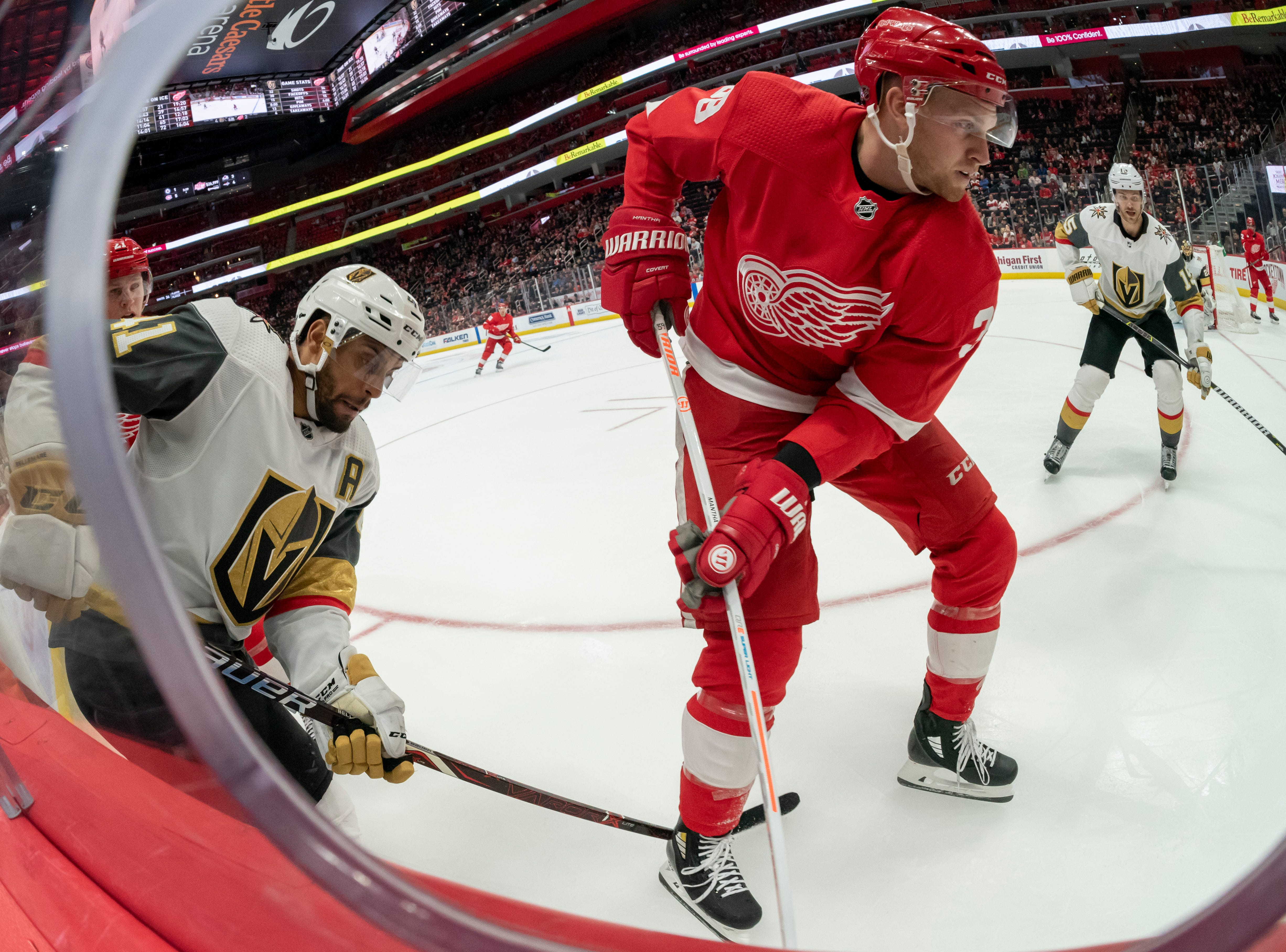 Vegas right wing Pierre-Edouard Bellemare and Detroit right wing Anthony Mantha battle for the puck in the third period.