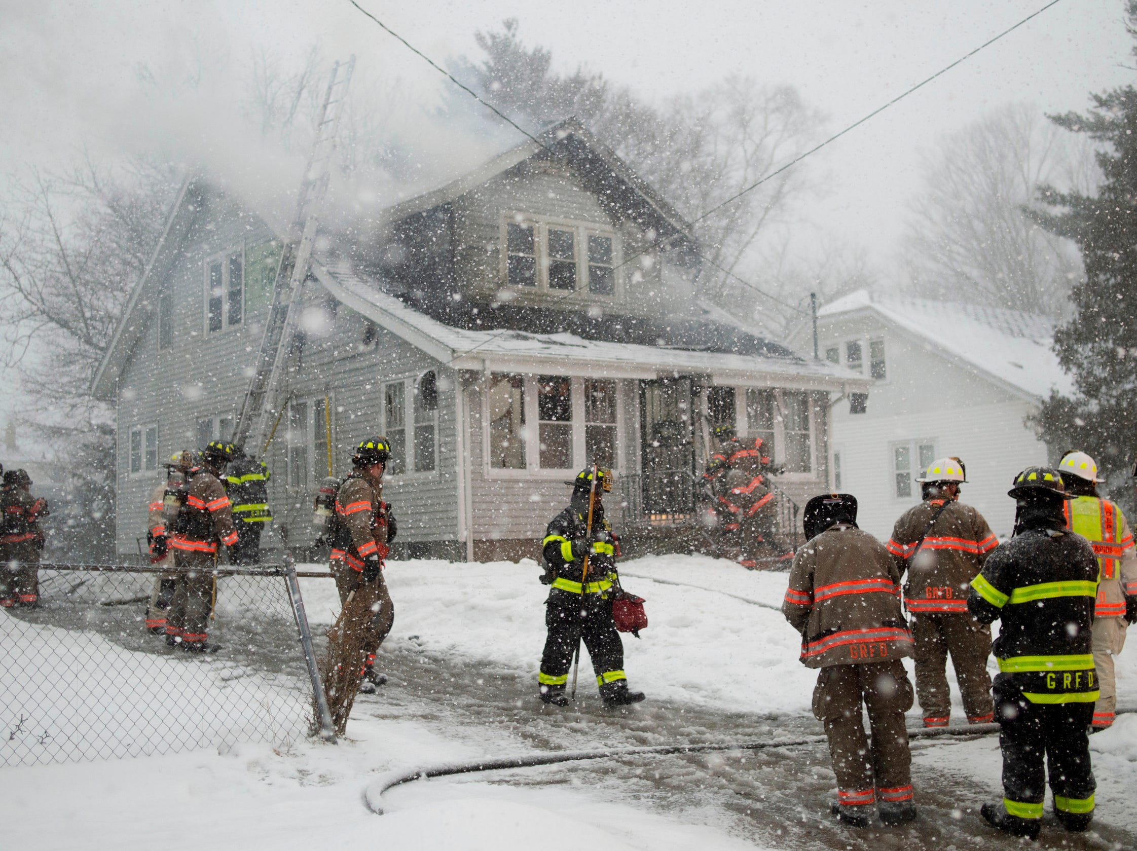Firefighters battle a house fire in Grand Rapids, Mich., on Friday, Feb. 8, 2019. The temperatures froze hydrants and complicated their response.
