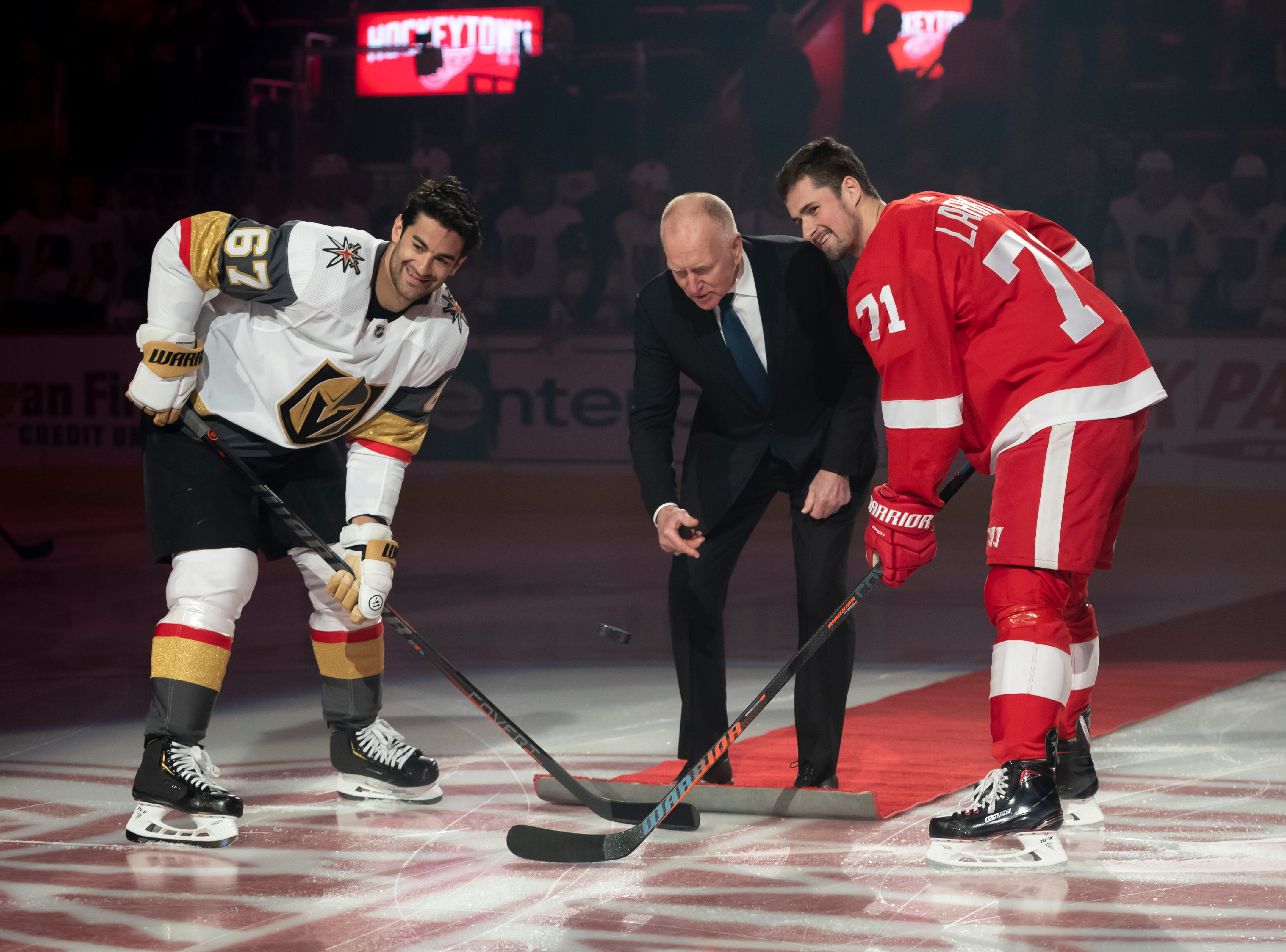 Former University of Michigan head hockey coach Red Berenson participates in a ceremonial puck drop with Vegas left wing Max Pacioretty and Detroit center Dylan Larkin before the start of the game.