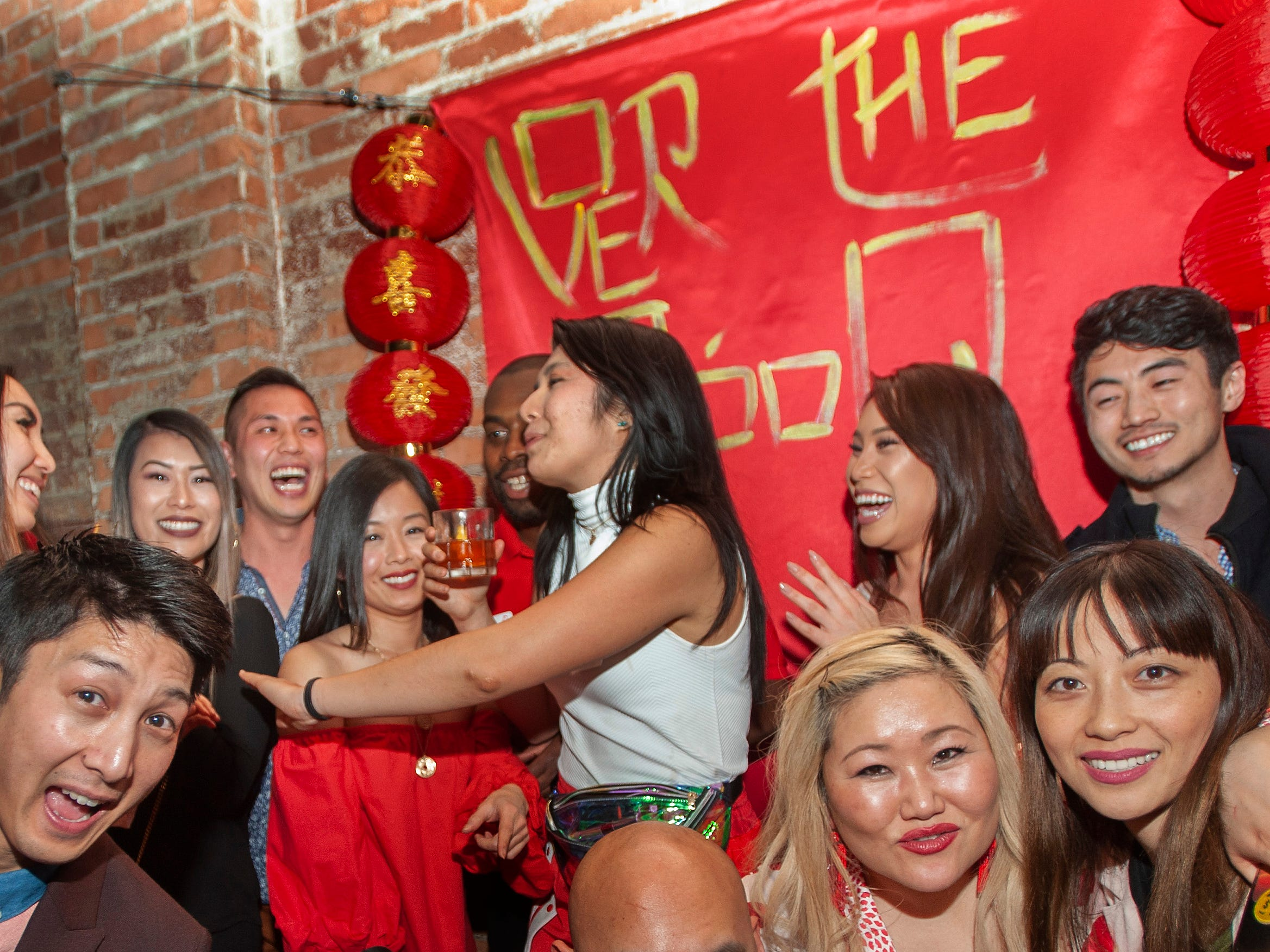 Over the Moon party goer David Tran (far left) of Windsor and party organizers Esther Kim of Grosse Pointe Farms (right) and Gowhnou Lee of Royal Oak (far right)  and others celebrate the Lunar New Year with an east-Asian style party at Detroit City Distillery in Eastern Market on Thursday, February 7, 2019.