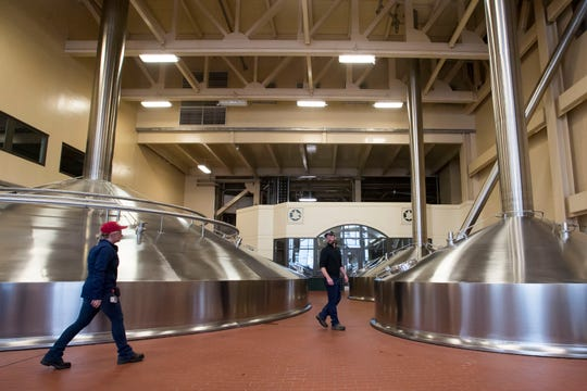 Utilities process engineer Tyler Gohlberg, right, and senior resident engineer Kim Jacobs walk through the kettle room of the brew house while leading a tour on Wednesday, Feb. 6, 2019, at the Anheuser Busch brewery in Fort Collins, Colo.