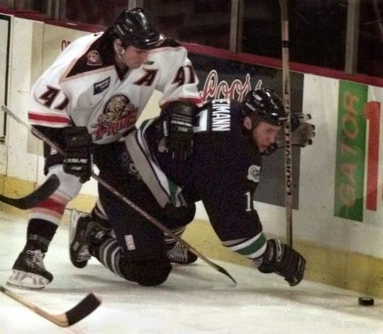 10-17-1998 1A; Florida Everblade Dan Reimann, right, is checked by Ryan Petz, of the Pee Dee Pride, during the first period of the Florida Everblades' season opening game against the Pee Dee Pride in Florence, South Carolina Friday night. The Everblades begin their inaugural season with 13 away games before finally playing a home game at their new arena in Estero November 19. BENJAMIN RUSNAK/News-Press