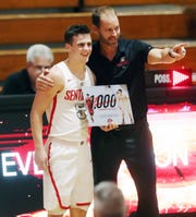 Evangelical Christian School's Chase Goodwin and coach Scott Guttery celebrate Goodwin scoring his 1,000-career point on Thursday against Oasis at ECS.