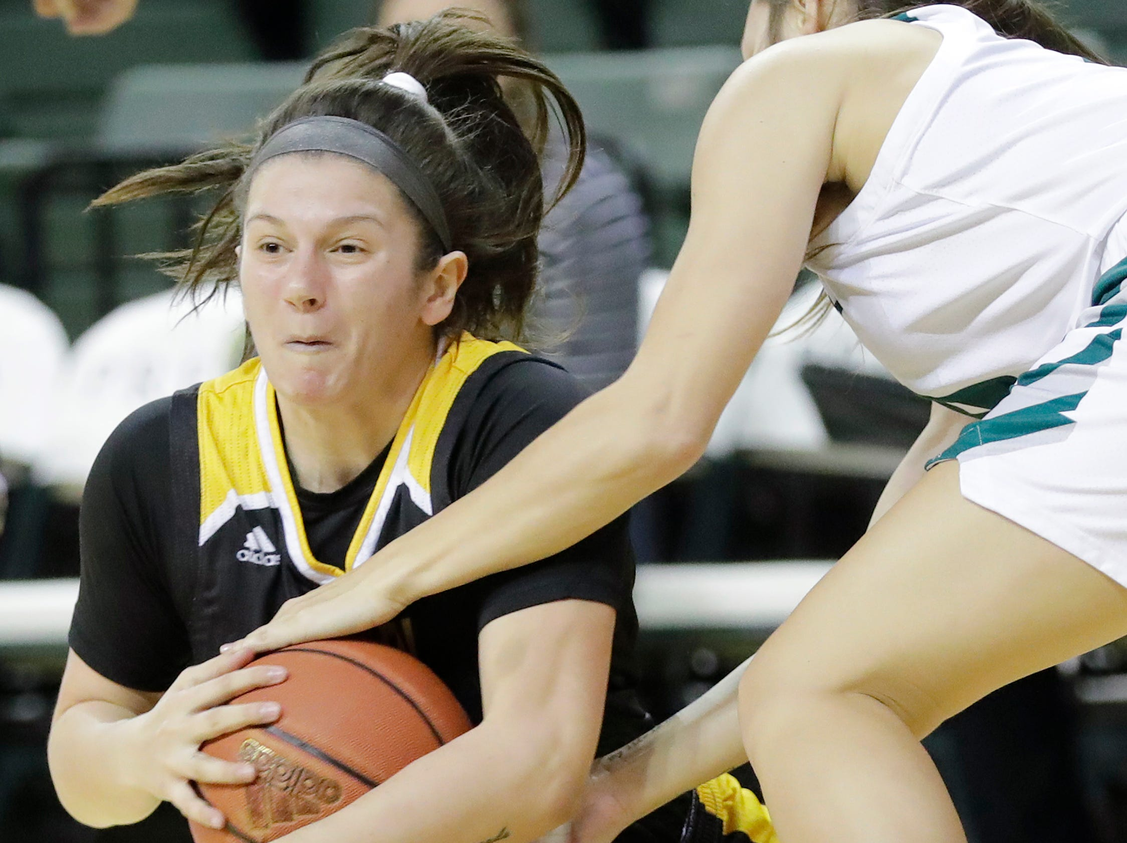 Northern Kentucky Norse forward Jazmyne Geist (left) dives for a loose ball against Green Bay Phoenix guard Hailey Oskey in a Horizon League women's basketball game at the Kress Center on Thursday, February 7, 2019 in Green Bay, Wis.