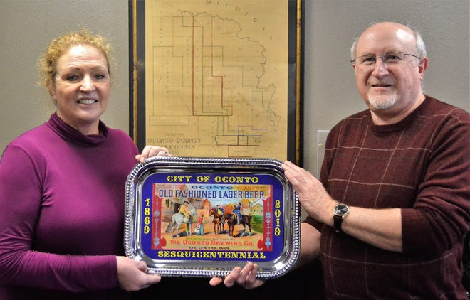 Oconto City Council member and Tourism Committe chairperson Jean Feldt and Oconto County HIstorical Society President Pete Stark hold a serving tray OCHS is selling as part of the city's sesquicentennial this year. The center of the tray is a laminated vinyl reproduction of an Oconto Beer label from more than 100 years ago.