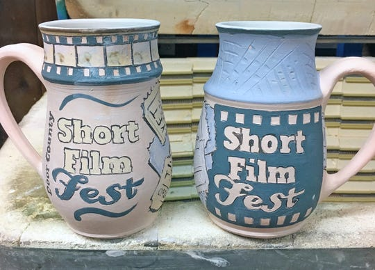 """The 2019 Juried and People's Choice Golden Mug Awards for the 2019 Door County Short Film Fest, handcrafted by Larry """"Thor"""" Thoreson of Gills Rock Pottery in Ellison Bay."""