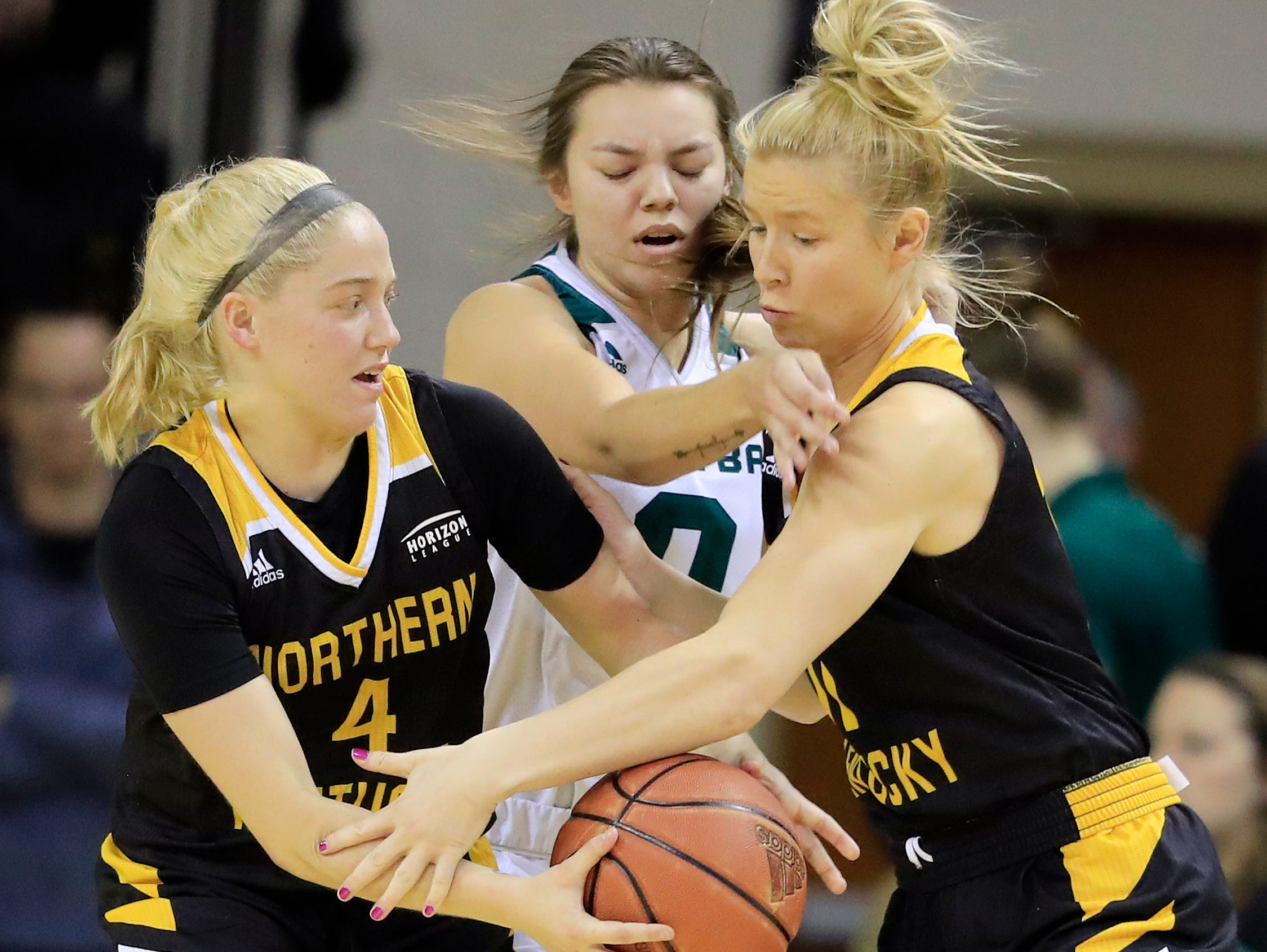 Northern Kentucky Norse guard Taryn Taugher (11) passes to guard Taylor Clos (4) against Green Bay Phoenix guard Hailey Oskey (0) in a Horizon League women's basketball game at the Kress Center on Thursday, February 7, 2019 in Green Bay, Wis.
