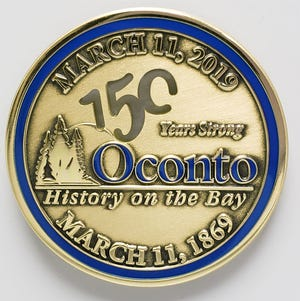 The front of a commemorative coin produced for the City of Oconto's 150th anniversary this year.