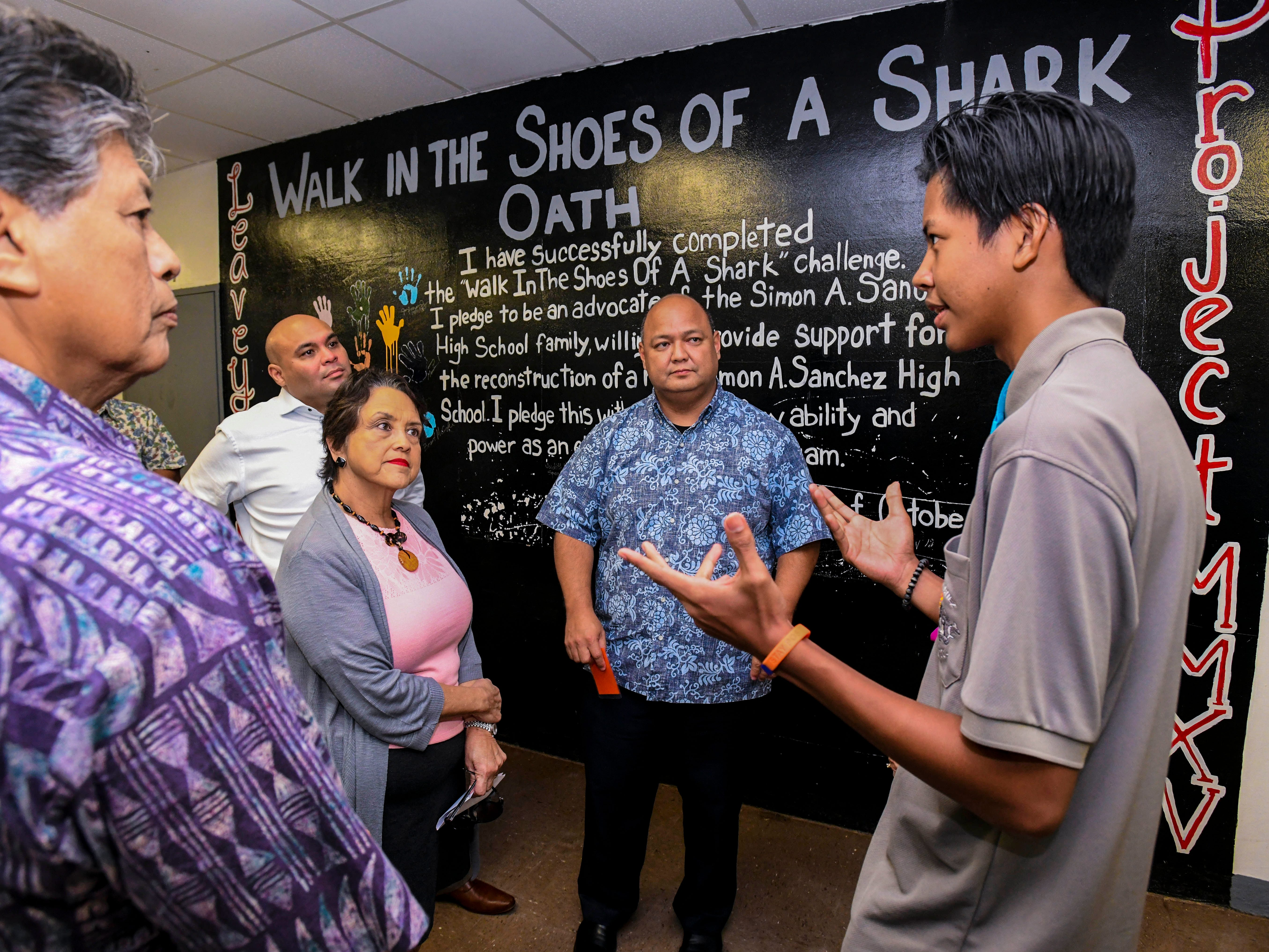 Devin Eligio, right, an Islandwide Board of Governing Students representative, takes a moment to chat with Gov. Lou Leon Guerrero, Lt. Gov. Josh Tenorio, Guam Department of Education Superintendent Jon Fernandez and other officials during their visit to the Simon Sanchez High School campus in Yigo on Friday, Feb. 8, 2019.