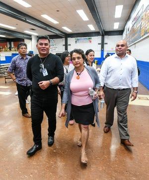 F.B. Leon Guerrero Middle School Principal Robert Martinez, right, escorts Gov. Lou Leon Guerrero, Lt. Gov. Josh Tenorio, education officials and others on a tour through the school campus in Yigo on Friday, Feb. 8, 2019.