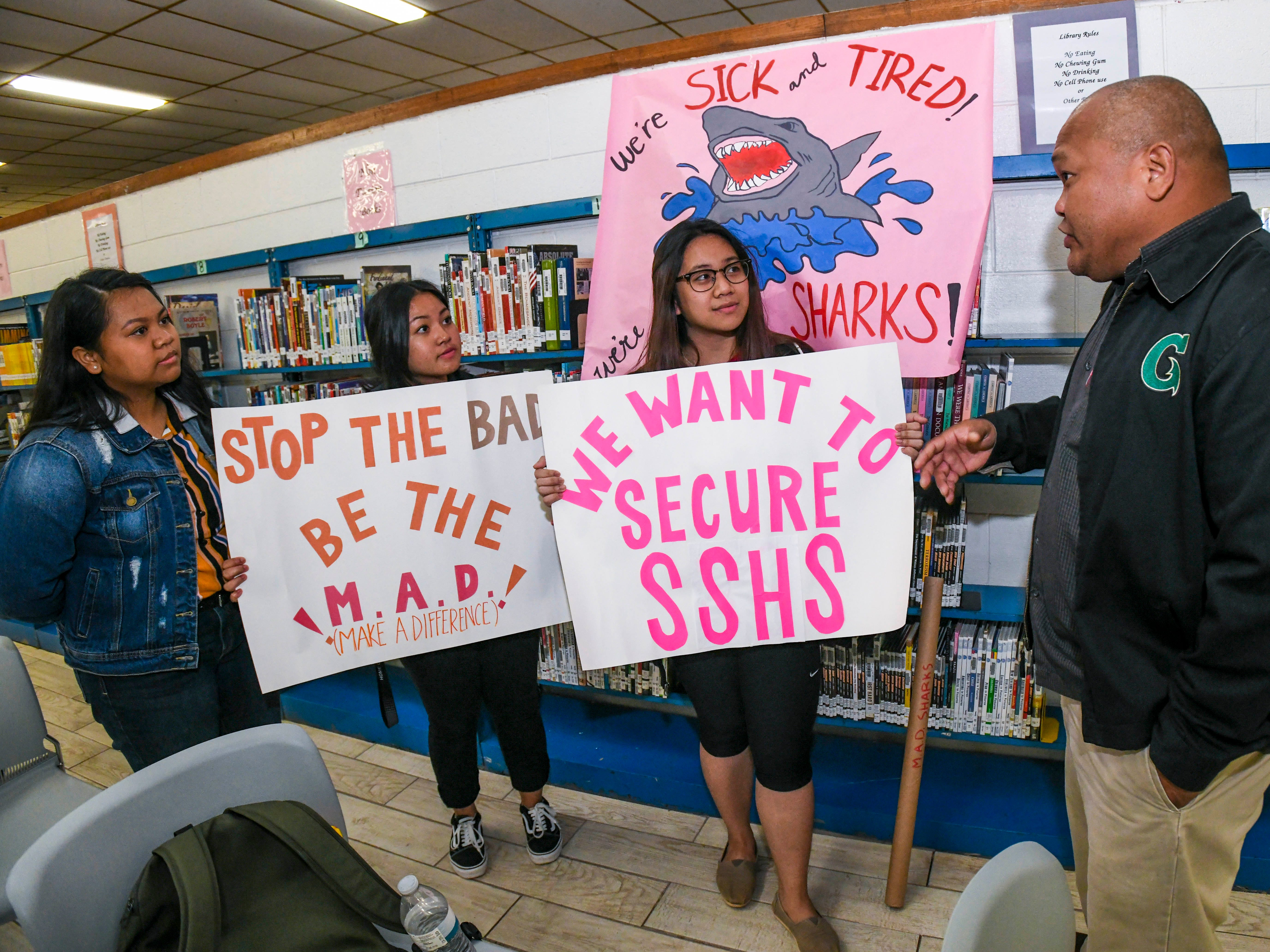 Guam Education Board Chairman Mark Mendiola, right, engages with students, from left, Tatiana Remoket, Maria Jayna Pico and Rovielynn Menrige, as they talk about improving the security and safety at the SImon Sanchez High School campus in Yigo on Friday, Feb. 8, 2019.