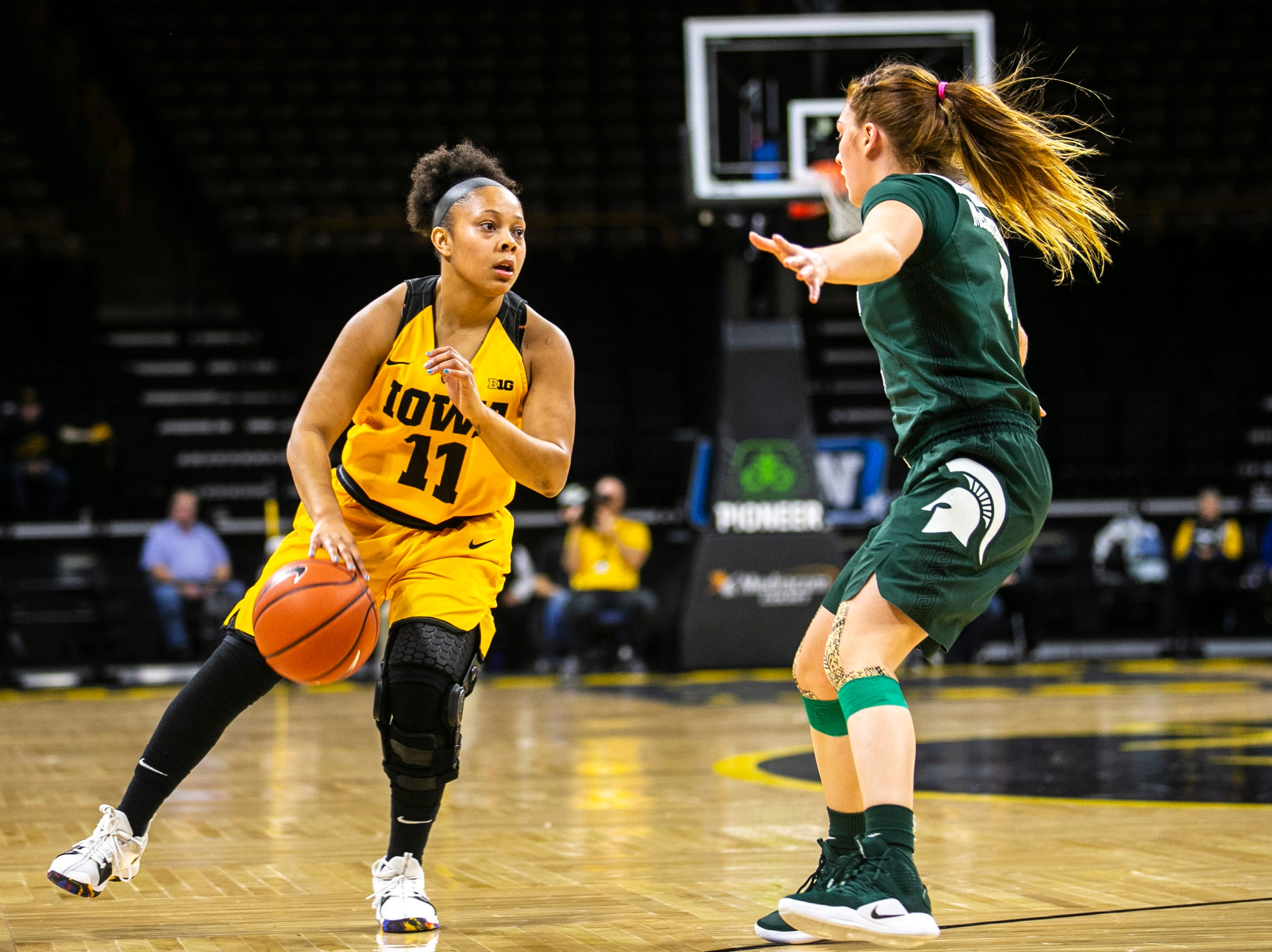 Iowa guard Tania Davis (11) takes the ball up court while Michigan State guard Taryn McCutcheon (4) defends during a NCAA Big Ten Conference women's basketball game on Thursday, Feb. 7, 2019 at Carver-Hawkeye Arena in Iowa City, Iowa.