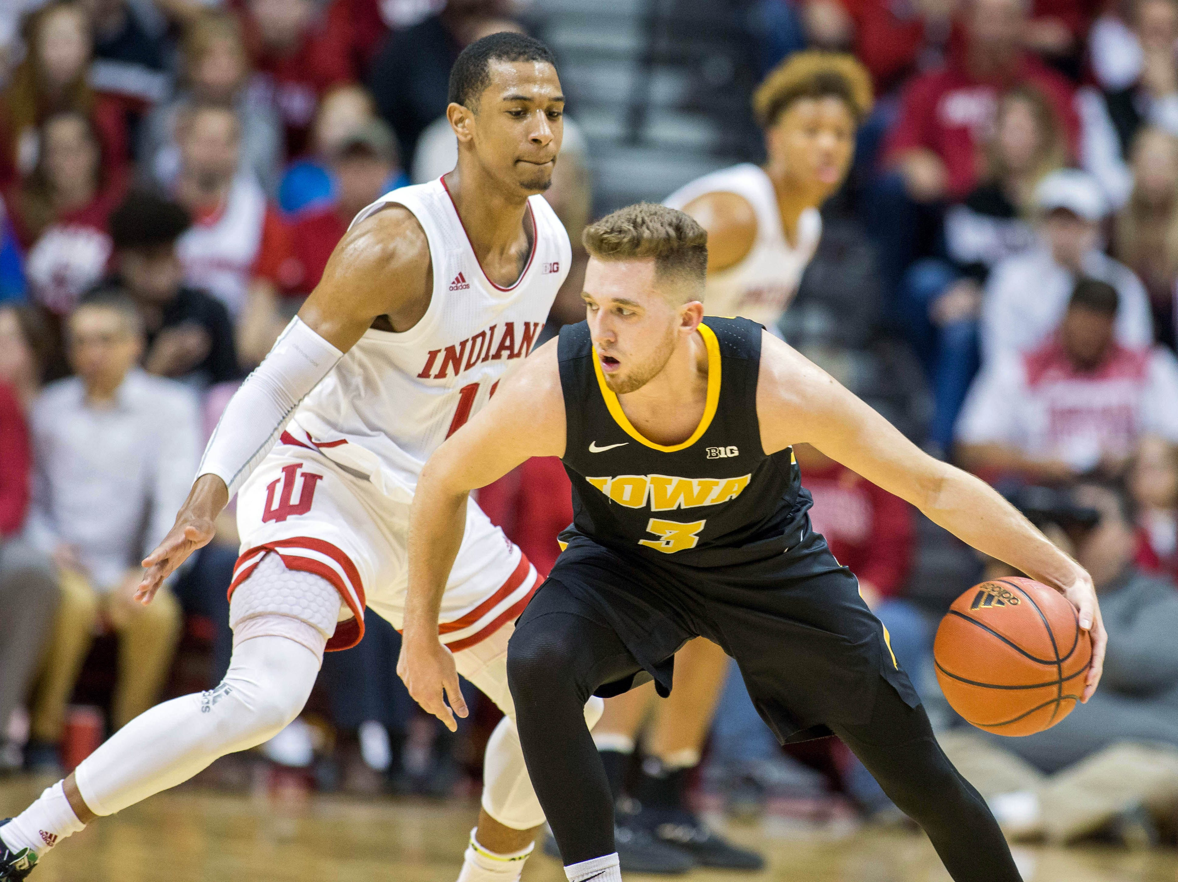 Iowa Hawkeyes guard Jordan Bohannon (3) dribbles the ball while Indiana Hoosiers guard Devonte Green (11) defends in the first half at Assembly Hall. Mandatory Credit: Trevor Ruszkowski-USA TODAY Sports