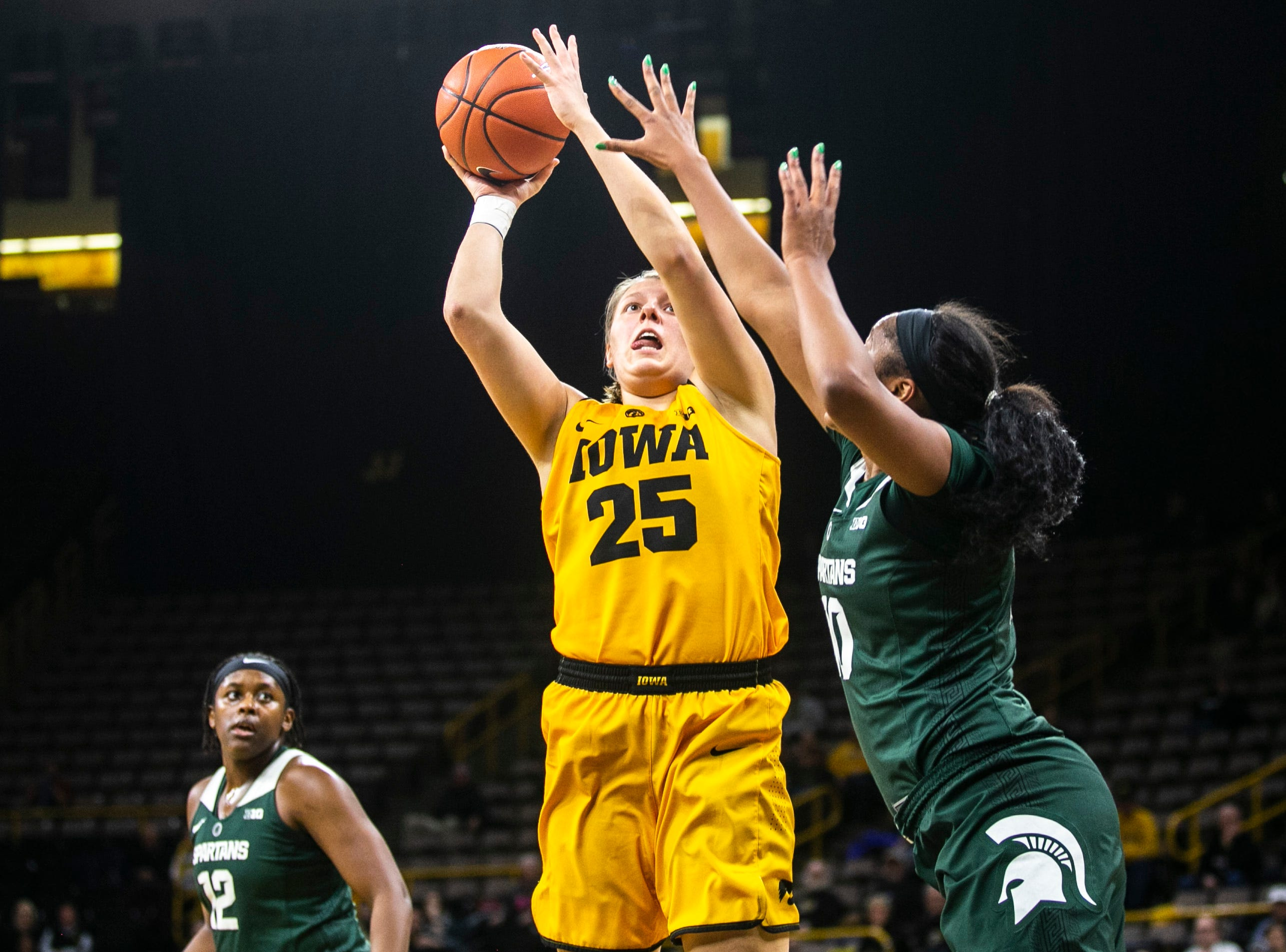 Iowa's Monika Czinano (25) gets defended by Michigan State forward Sidney Cooks (10) during a NCAA Big Ten Conference women's basketball game on Thursday, Feb. 7, 2019 at Carver-Hawkeye Arena in Iowa City, Iowa.