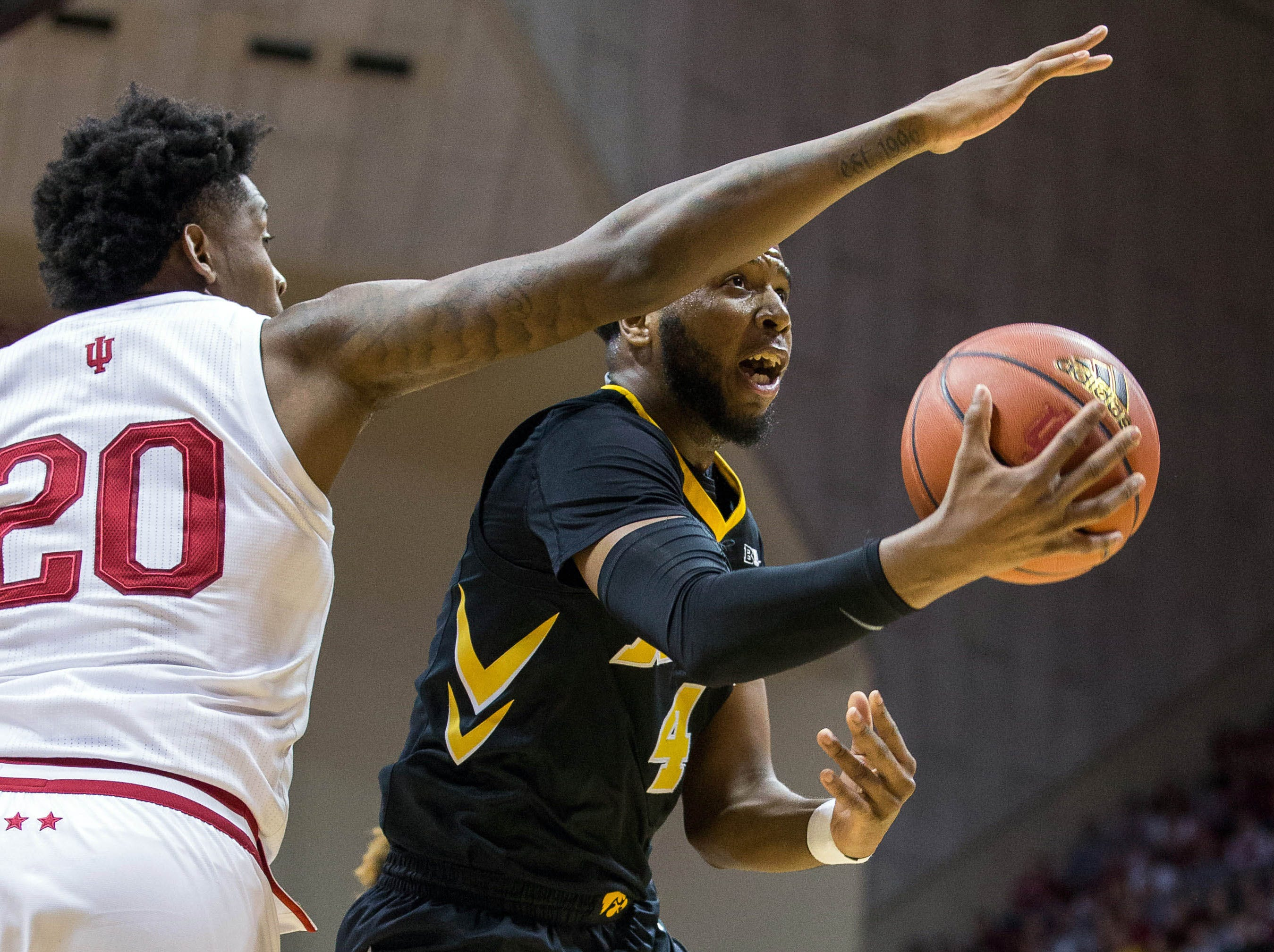 Iowa Hawkeyes guard Isaiah Moss (4) shoots the ball while Indiana Hoosiers forward De'Ron Davis (20) defends in the second half at Assembly Hall. Mandatory Credit: Trevor Ruszkowski-USA TODAY Sports