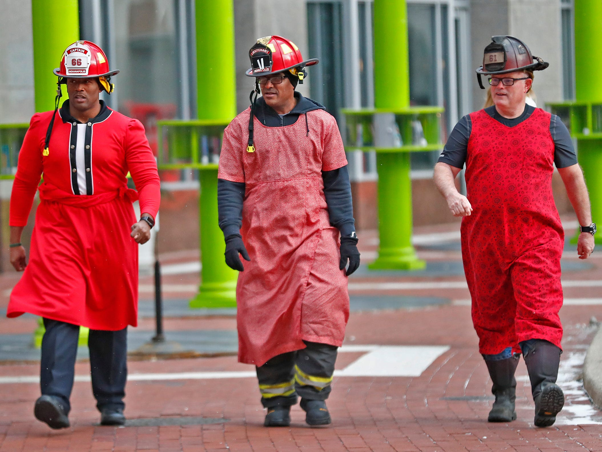 IFD's Corey Floyd, from left, Willie Thompson, and Jim King don red dresses to walk around Monument Circle for the Red Dress Dash, Friday, Feb. 8, 2019.  The American Heart Association put on the seventh annual event to support women's heart health.  The event raises awareness for the American Heart Association's Go Red For Women movement.  Heart disease is the leading cause of death among women.