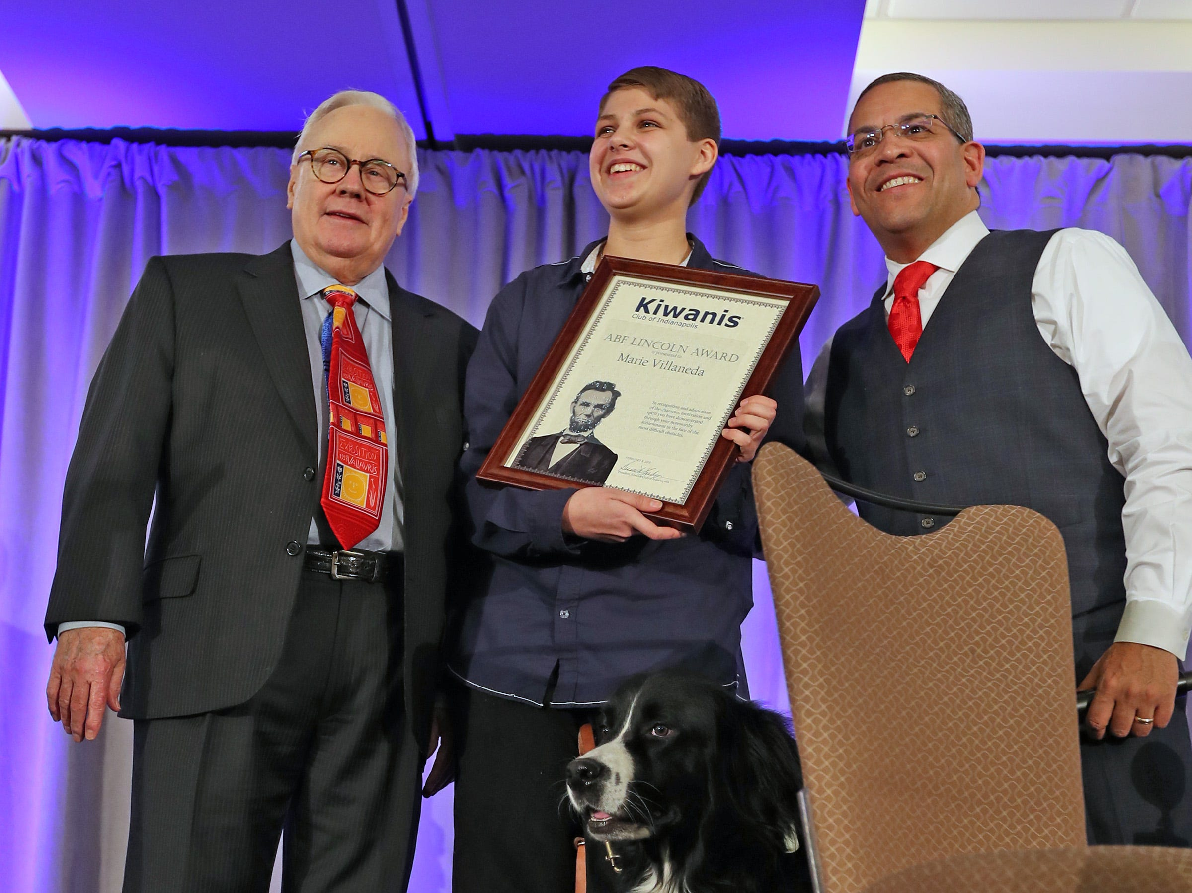 Marie Villaneda, center, is presented the 3rd Place Scholarship award at the 44th Annual Abe Lincoln Awards Program, Friday, Feb. 8, 2019. The Indiana School for the Blind & Visually Impaired student stands with Chic Born, left, Rafael Sanchez, right, and her service dog, Bear.  The Kiwanis Club of Indianapolis program was held at Ivy Tech Community College.  20 high school student were honored at the annual event which celebrates overcoming adversity in life to succeed.  Four of the 20 students were given scholarships.