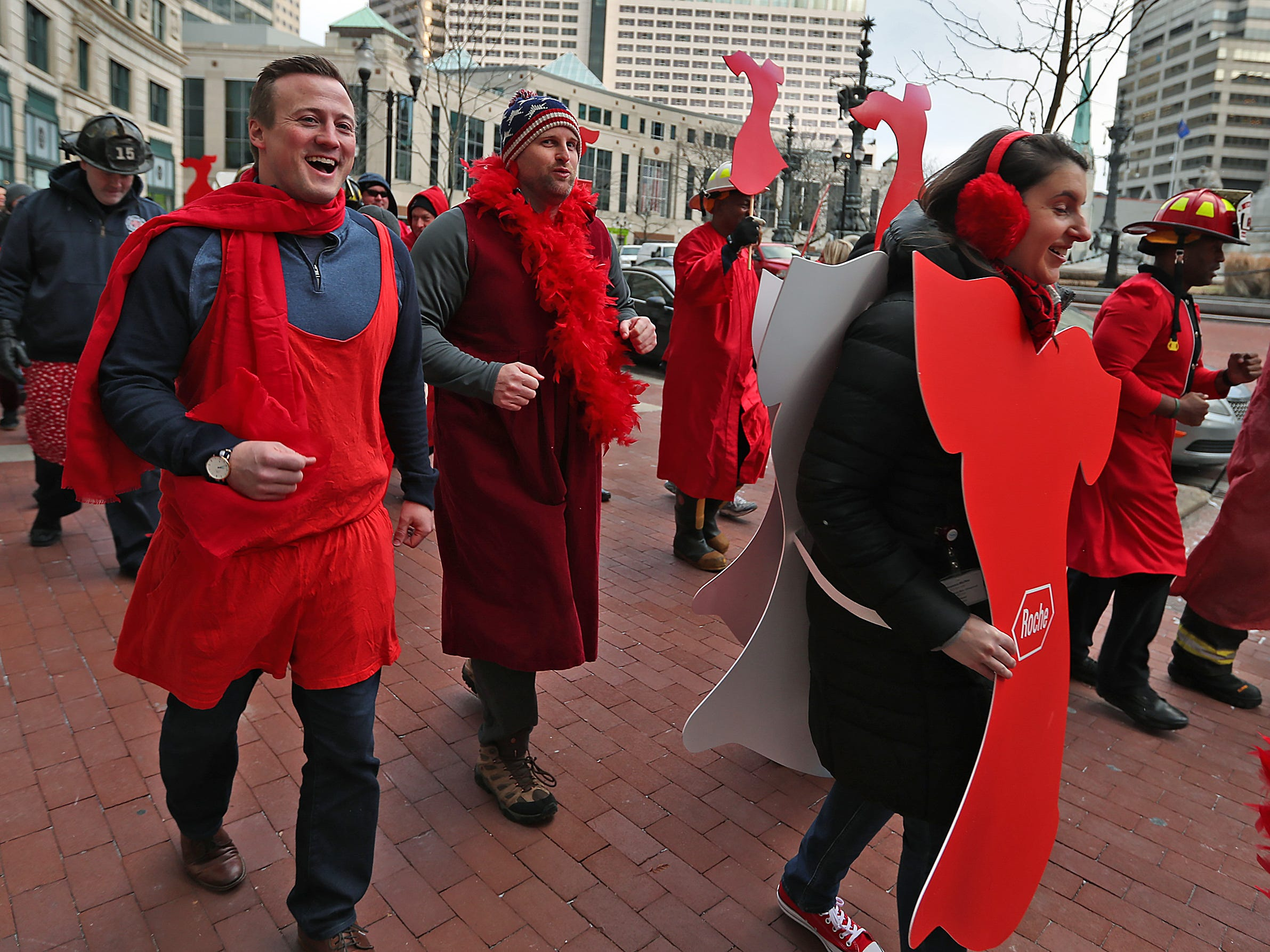 Patrick Triest, left, Bryan Hohne, both with J.D. Byrider, and Kelsey Hobbs, from Roche, join others in red as they walk and dash around Monument Circle for the Red Dress Dash, Friday, Feb. 8, 2019.  The American Heart Association put on the seventh annual event to support women's heart health.  The event raises awareness for the American Heart Association's Go Red For Women movement.  Heart disease is the leading cause of death among women.