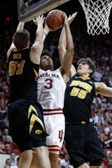 Indiana forward Justin Smith (3) shoots between Iowa defenders Nicholas Baer (51) and Luka Garza (55) during the second half of an NCAA college basketball game in Bloomington, Ind., Thursday. Iowa won 77-72.