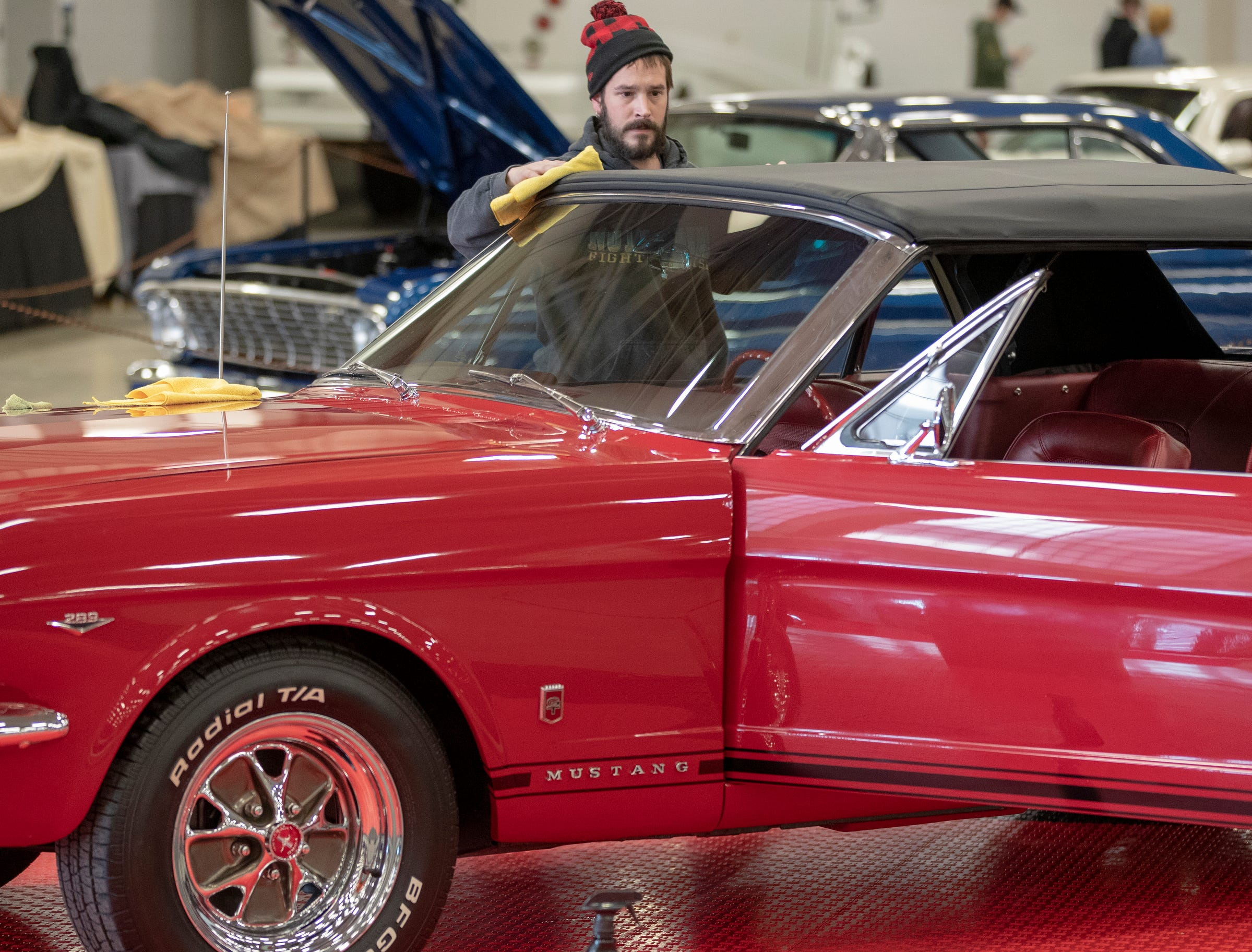 Kyle Huffaker works on polishing a 1966 Ford Mustang, at World of Wheels at the Indiana State Fairgrounds, Indianapolis, Friday, Feb. 8, 2019. The event runs through the weekend and features four big rooms of stock and heavily customized cars.