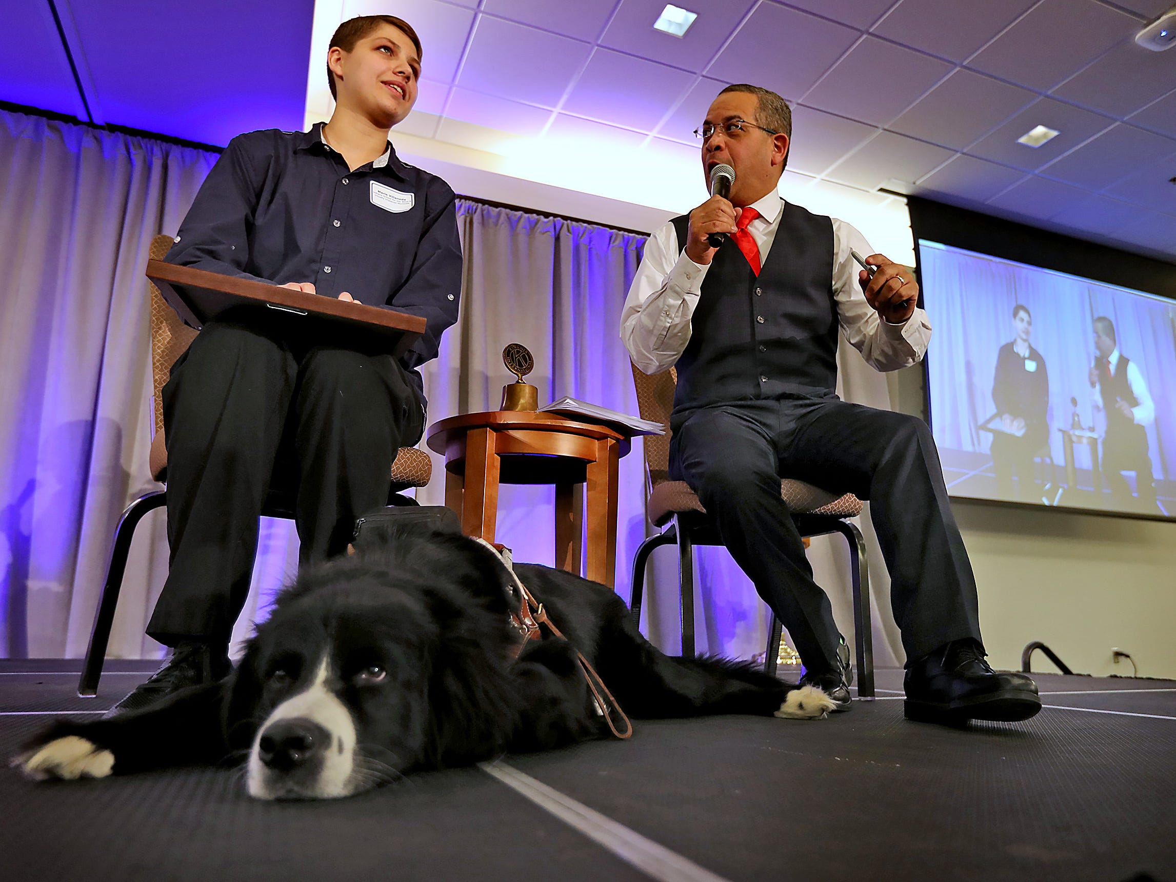 Indiana School for the Blind & Visually Impaired student Marie Villaneda, left, sitting with her guide dog Bear, is interviewed by Rafael Sanchez after being presented the 3rd Place Scholarship award at the 44th Annual Abe Lincoln Awards Program, Friday, Feb. 8, 2019. The Kiwanis Club of Indianapolis program was held at Ivy Tech Community College.  20 high school student were honored at the annual event which celebrates overcoming adversity in life to succeed.  Four of the 20 students were given scholarships.