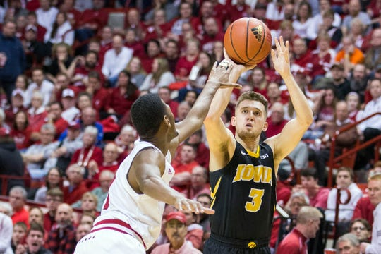 Hawkeyes guard Jordan Bohannon (3) shoots a three point basket while Indiana Hoosiers guard Aljami Durham (1) defends in the second half at Assembly Hall.