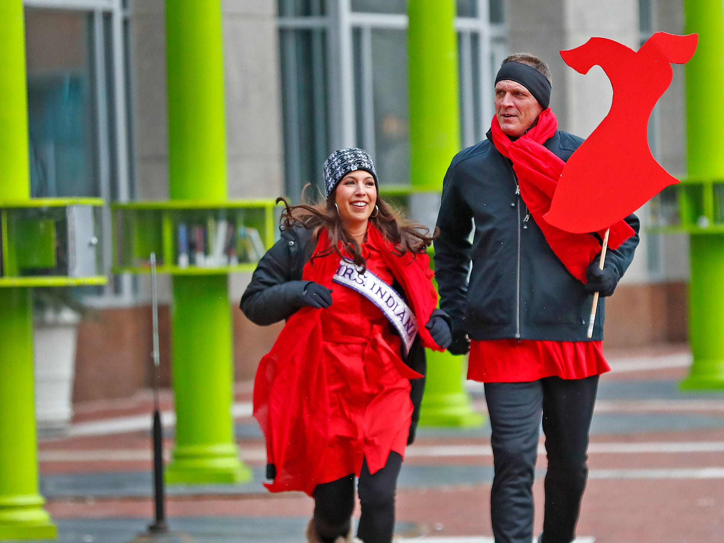 Mrs. Indiana International Lauren Hughes, left, and her husband Chris Hughes join others as they walk around Monument Circle for the Red Dress Dash, Friday, Feb. 8, 2019.  The American Heart Association put on the seventh annual event to support women's heart health.  The event raises awareness for the American Heart Association's Go Red For Women movement.  Heart disease is the leading cause of death among women.