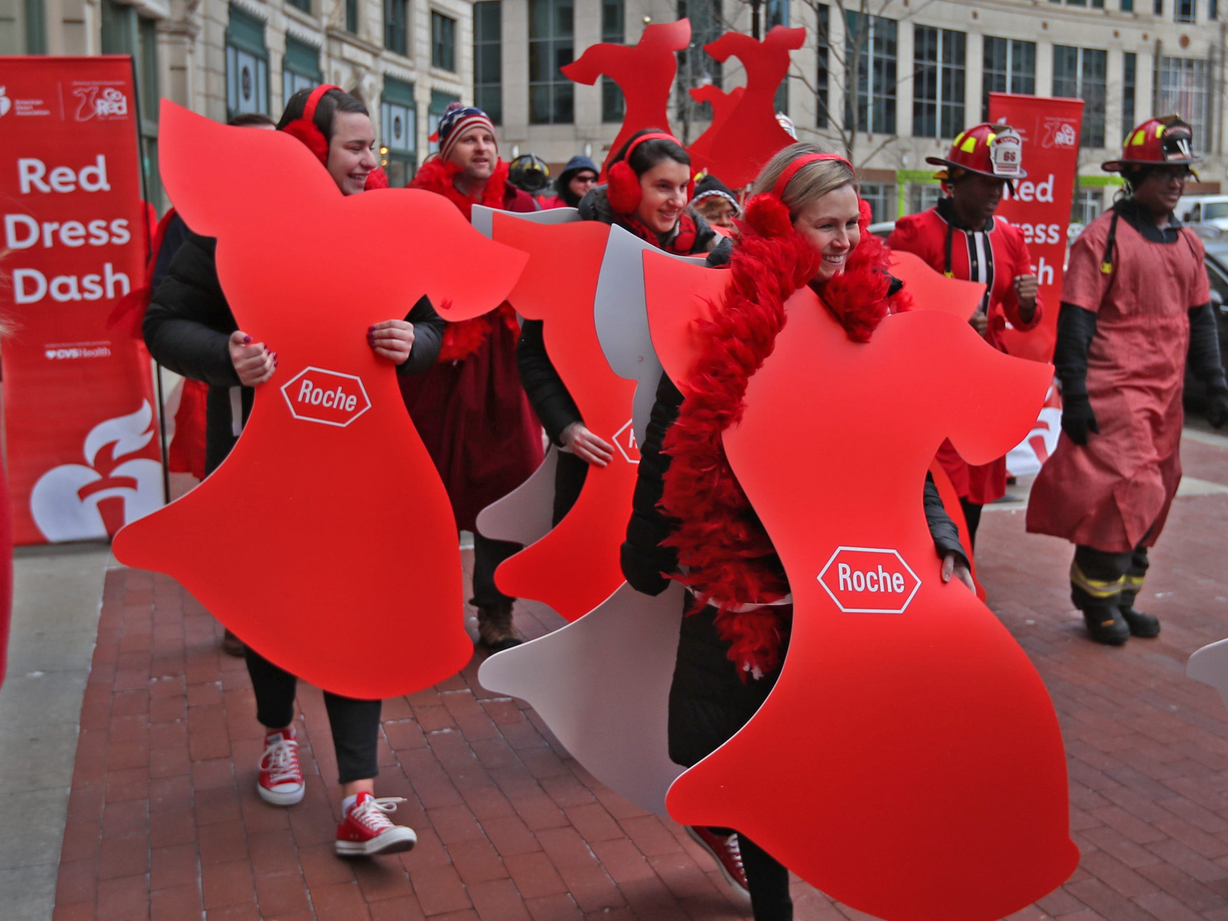 Maggie Sullivan, from left, Kelsey Hobbs and Courtney Sweeney, from Roche, join others in red as they walk around Monument Circle for the Red Dress Dash, Friday, Feb. 8, 2019.  The American Heart Association put on the seventh annual event to support women's heart health.  The event raises awareness for the American Heart Association's Go Red For Women movement.  Heart disease is the leading cause of death among women.
