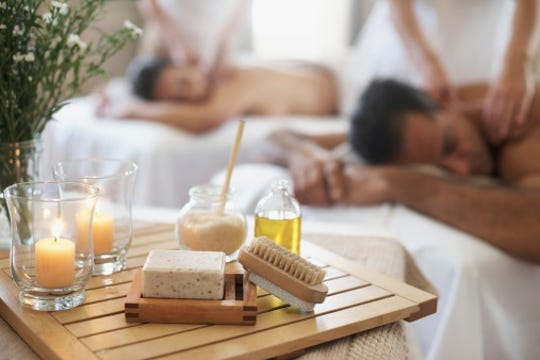Shot of an assortment of massage related products with a couple enjoying one in the background