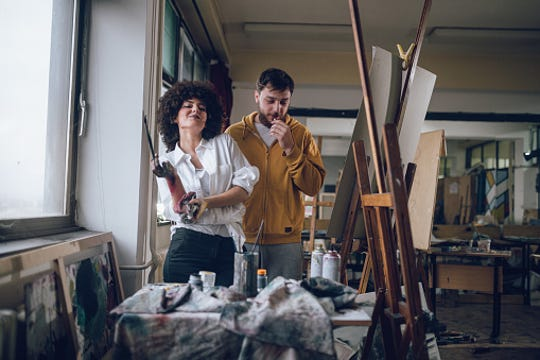 Gorgeous looking artist couple, painting at the art studio, living the painters lifestyle.