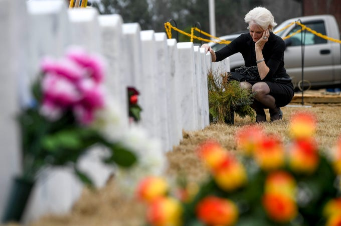 """Kimberlee Bauer, an Air Force veteran, places her hand on the grave of her deceased husband, who passed away in November after a fight with terminal brain cancer before attending a funeral for Sgt. Mary Nolen, a military veteran with no known family at Tennessee State Veterans Cemetery in Parkers Crossroads, Tenn., on Thursday, Feb. 7, 2019. """"I only live three or four miles away, I visit him every day,"""" Bauer said."""