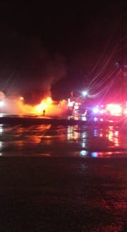 A fireman walks near the site of the burning Super-Lube auto shop on North Parkway in Jackson on Thursday night.