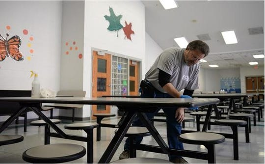 Ken Spencer, a custodial foreman with Knox County Schools, cleans a table in the Christenberry Elementary School cafeteria on Friday, Feb. 8, 2019. Knox County Schools were closed on Thursday and Friday to due excessive illness.