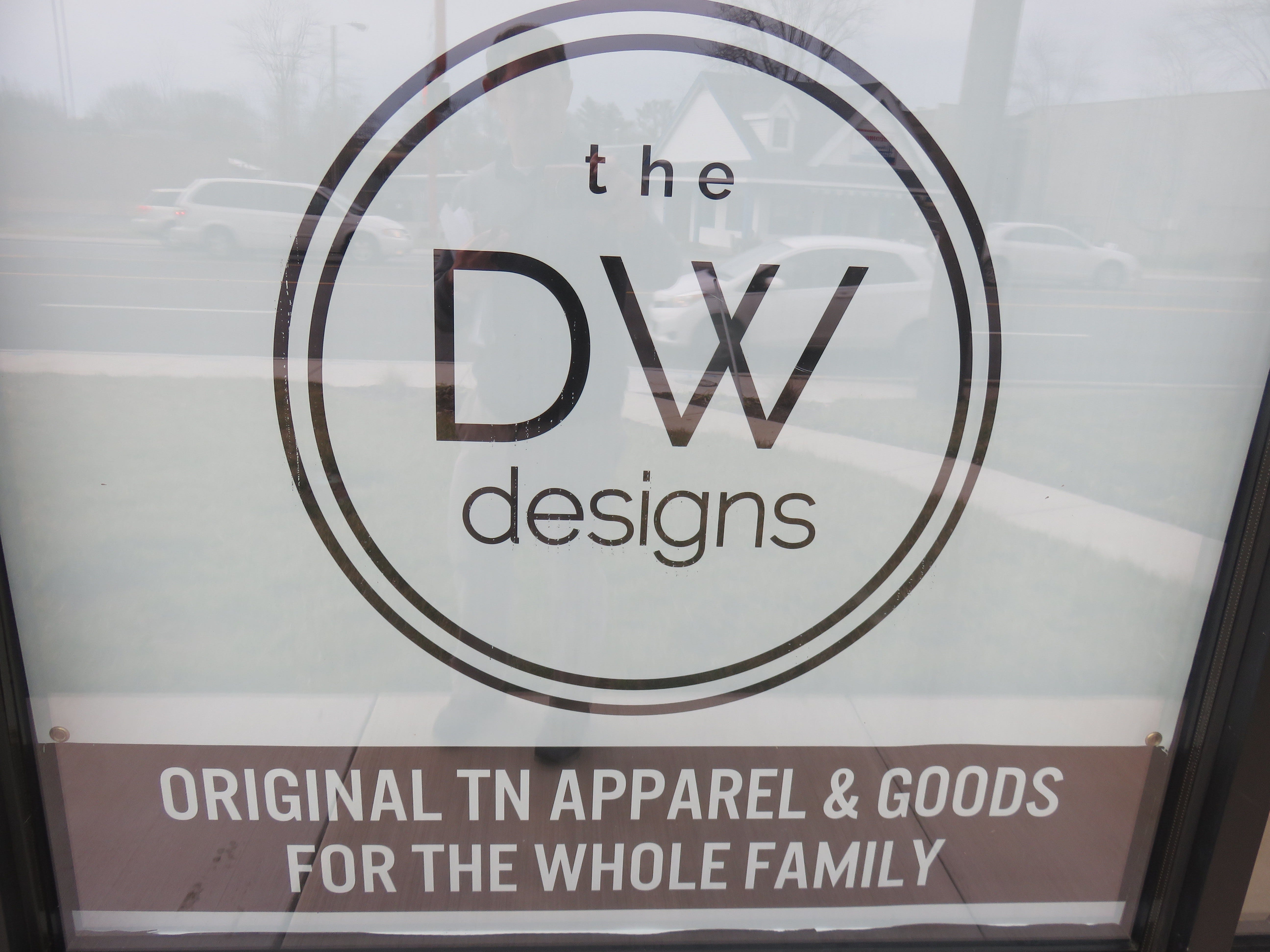 A sign advertising the new business hangs on the glass front of the building.