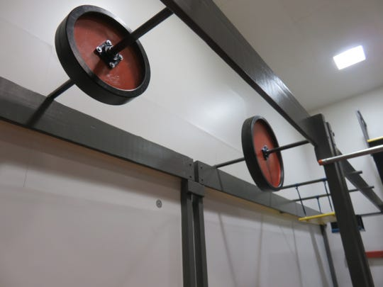 Barbell-like swings are among the obstacles in Ninja Gym