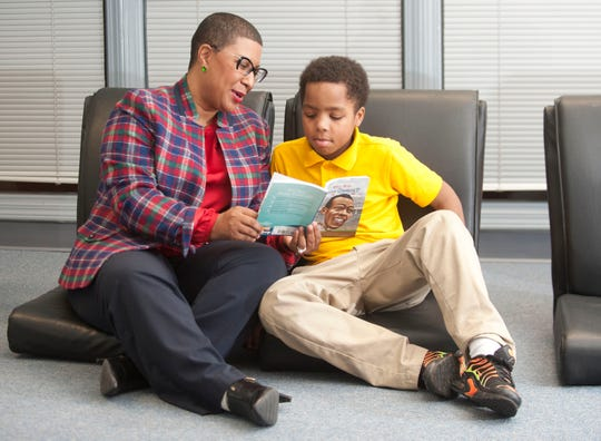 At the Sons of Issachar Academy, (an after-school mentoring program), Terra Leavell, chief executive officer and president of the Black Community Development Corporation (of Louisville,) helps 4th grader Patrick Webster read a book about famed Olympic gold medalist Jesse Owens.