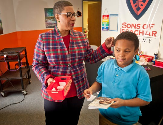 Terra Leavell, chief executive officer and president of the Black Community Development Corporation fondly strokes the head of 3rd grader Randy Adkins, age 9, at the Sons of Issachar Academy, (an after-school mentoring program.) Adkins pulled a reading assignment on historic Black men from a box held by Leavell. His book assignment was famed agricultural scientist and inventor George Washington Carver.