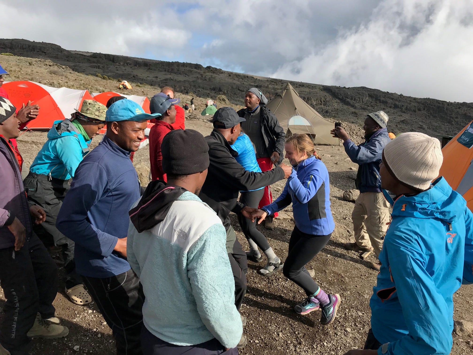 Jordan Grantz dancing wth porters on Mount Kilimanjaro, Tanzania