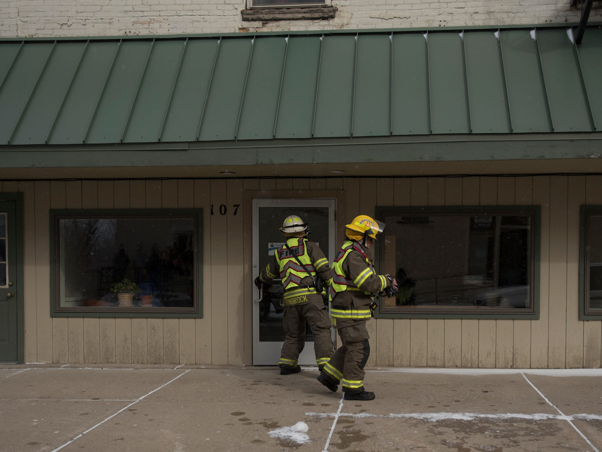 Firefighters go door-to-door at businesses and residences in downtown Portland, Michigan, near Kent St. and E. Grand River evacuating people as smoke was reported in a building along Kent St.  [Matthew Dae Smith/Lansing State Journal]