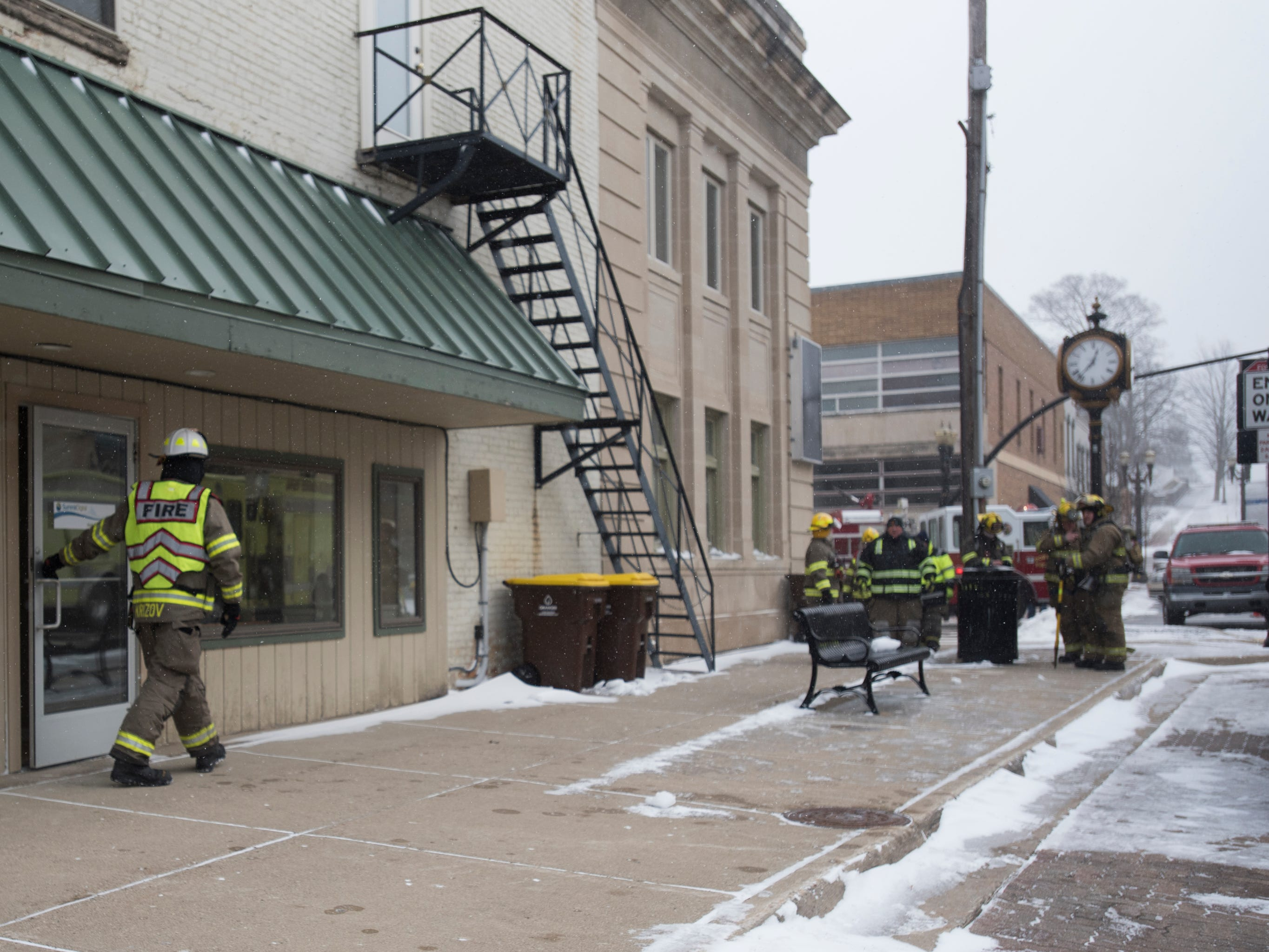 Firefighters go door-to-door at businesses and residences in downtown Portland, Michigan, near Kent Street and East Grand River River, evacuating people as smoke was reported in a building along Kent Street.