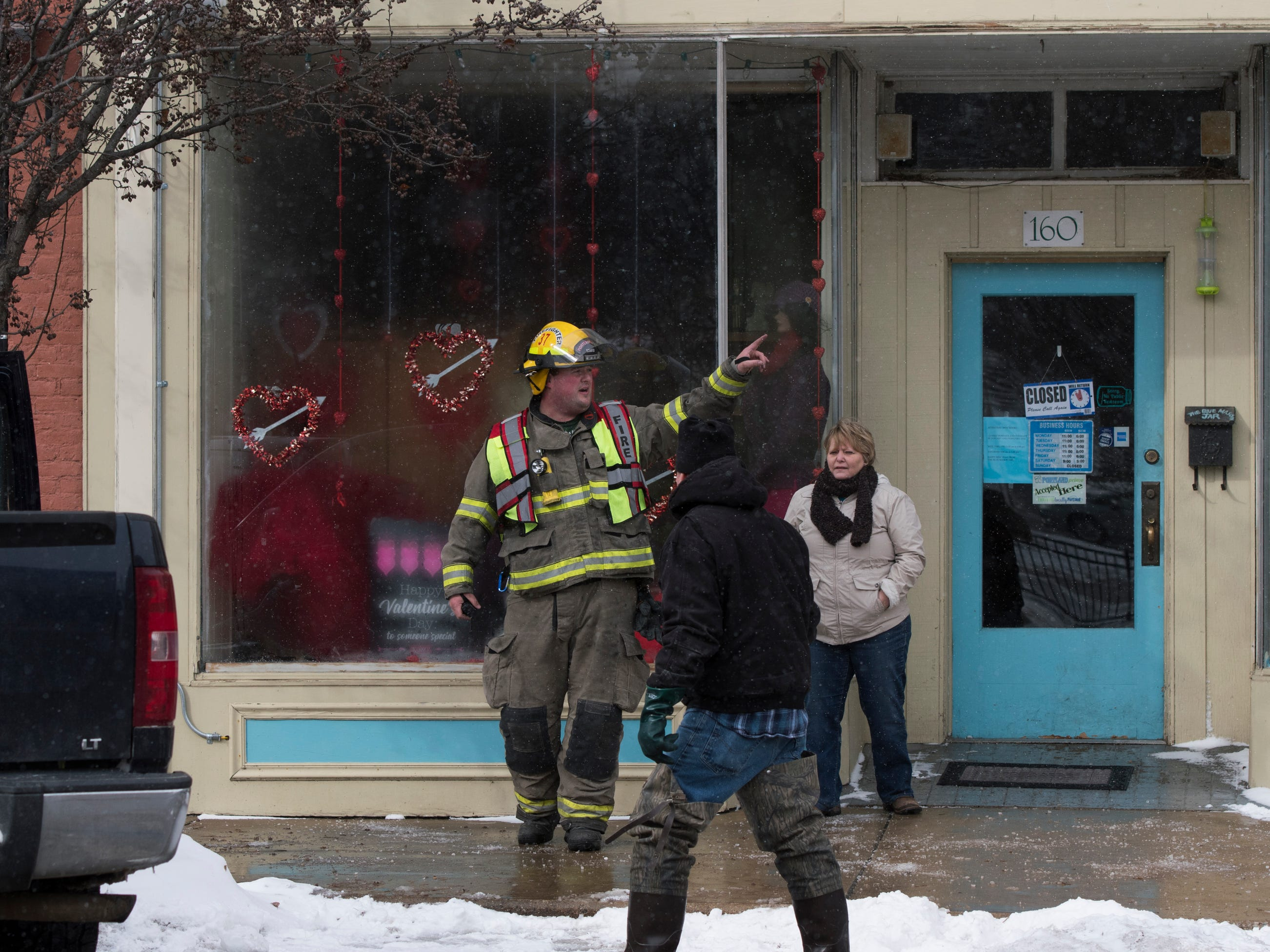 Firefighters go door-to-door at businesses and residences in downtown Portland, Michigan, near Kent Street and East Grand River Avenue evacuating people as smoke was reported in a building along Kent Street.