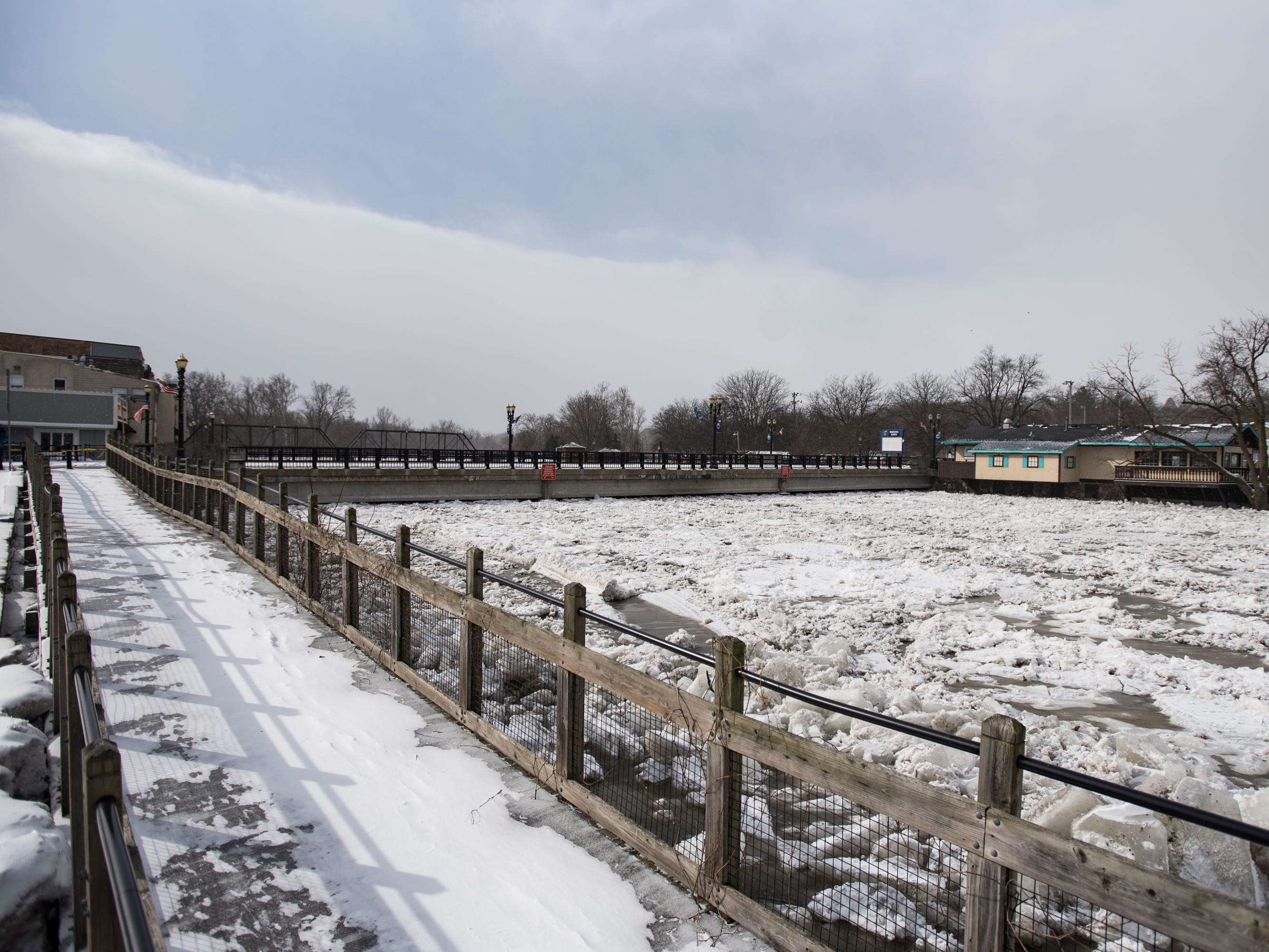 Ice jams can be seen at the bottom of the bridge that was closed Friday, Feb. 8, 2019, in downtown Portland, Michigan. Ice jams and rising waters threaten the integrity of the bridge.