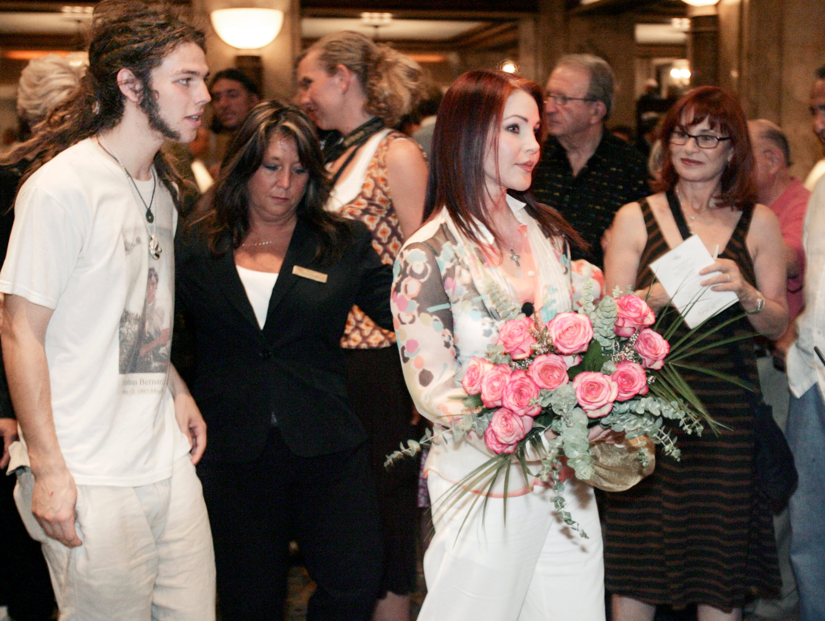 Priscilla Presley, front right, leaves the Peabody Hotel on Aug. 16, 2007, with her son, Navarone Garibaldi, left, on the 30th anniversary of the death of Elvis Presley, her former husband. Priscilla Presley was at the hotel for a ceremony inducting Elvis Presley into the hotel's Duck Walk Hall of Fame.