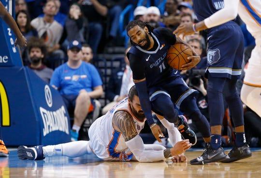 Memphis Grizzlies guard Mike Conley (11) moves around Oklahoma City Thunder center Steven Adams, left, during the first half of an NBA basketball game in Oklahoma City, Thursday, Feb. 7, 2019. (AP Photo/Sue Ogrocki)