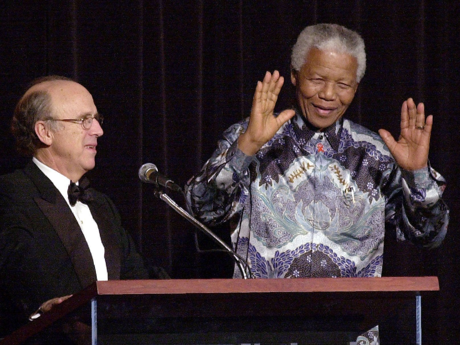 """Former president of South Africa Nelson Mandela, right, raises his hands to a standing ovation at The Peabody on Nov. 21, 2000, as he receives the National Civil Rights Museum's International Freedom Award. Looking on is AutoZone founder J.R. """"Pitt"""" Hyde."""