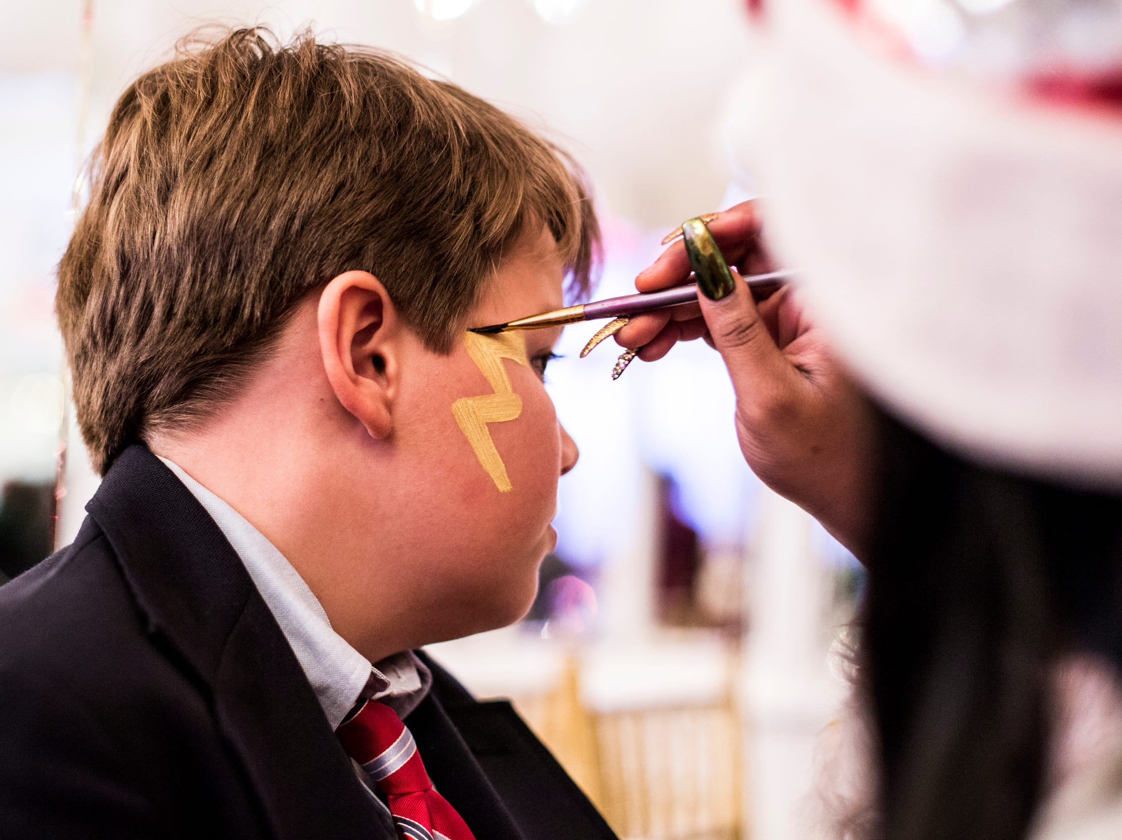 Garrett Johnson, 10, gets a lightning bolt painted on his face during the Memphis Jingle Bell Ball Holiday Cookie Party inside of the Continental Ballroom at the Peabody Hotel on Dec. 2, 2018. This was the 30th anniversary of the Jingle Bell Ball.