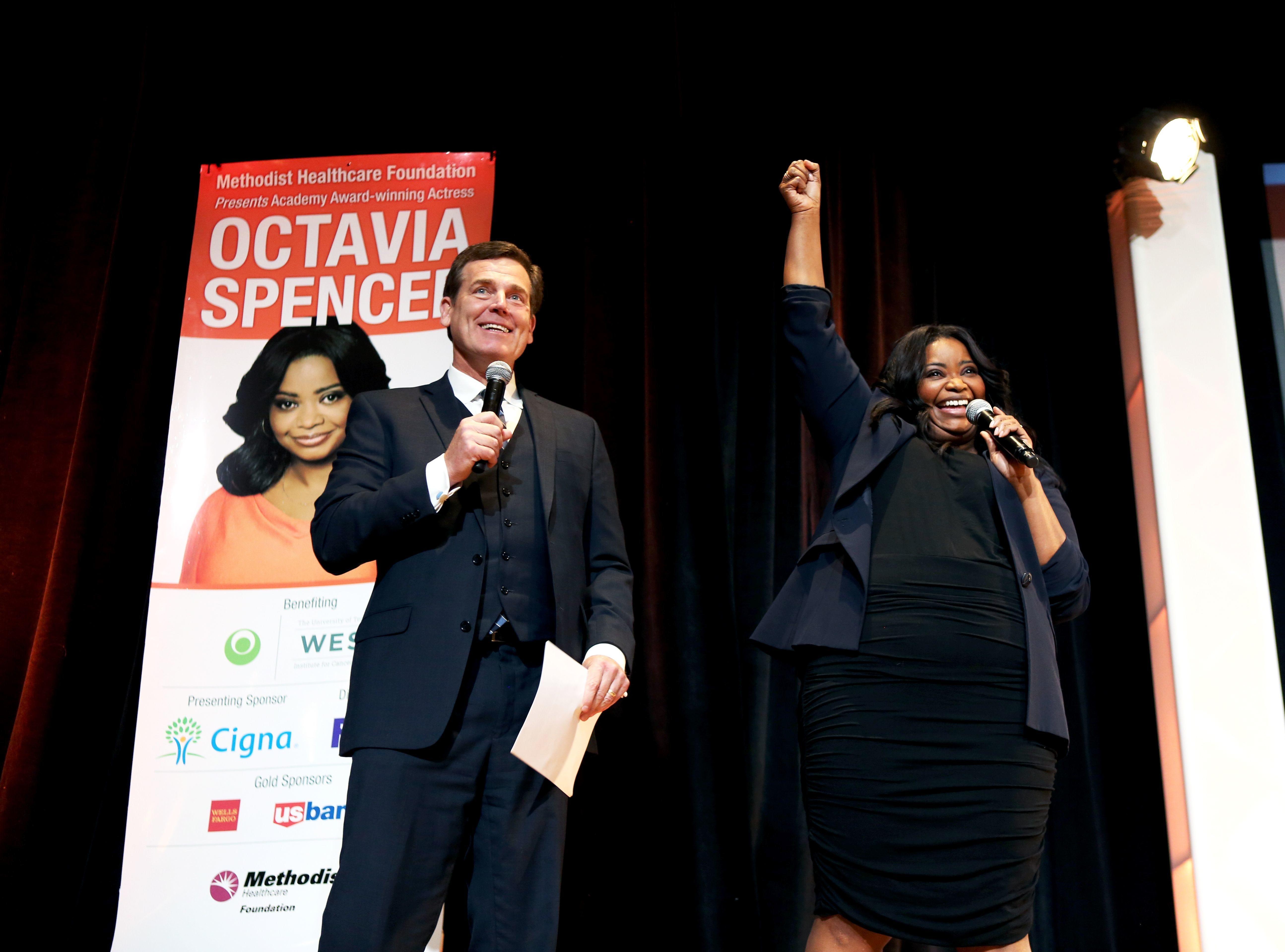 """Academy Award-winning actress Octavia Spencer raises her fist Nov. 28, 2017, and says """"War Eagle"""" after WMC Action News 5 co-anchor Joe Birch, left, mentions Auburn University's win over the University of Alabama in last weekend's 2017 Iron Bowl between the two football teams. Spencer, who graduated from Auburn in 1994, was the guest speaker during the 16th Annual Methodist Healthcare Foundation Cancer Center Luncheon in the Grand Ballroom of The Peabody Hotel."""