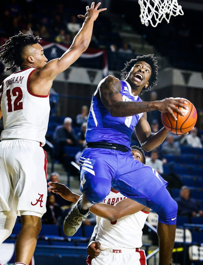 University of Memphis guard Kareem Brewton Jr. (right) drives for a layup against University of Alabama defender Dazon Ingram (left) during first half action at the Veterans Classic  in Annapolis, Md., Friday, November 10, 2017.