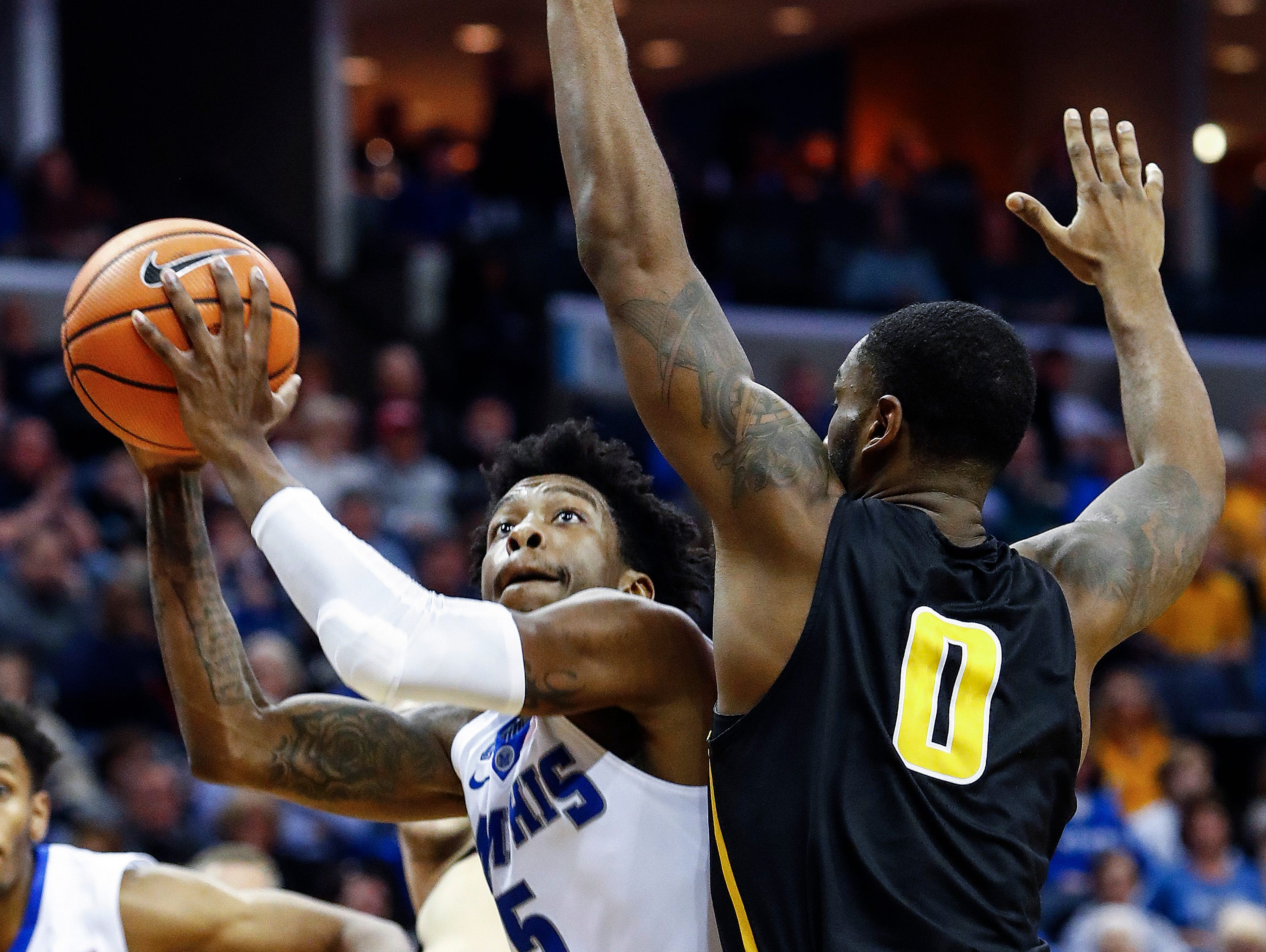 Memphis guard Kareem Brewton Jr. (left) drives for a layup against the Wichita State defense during second half action at the FedExForum in Memphis Tenn., Tuesday, February 6, 2018.