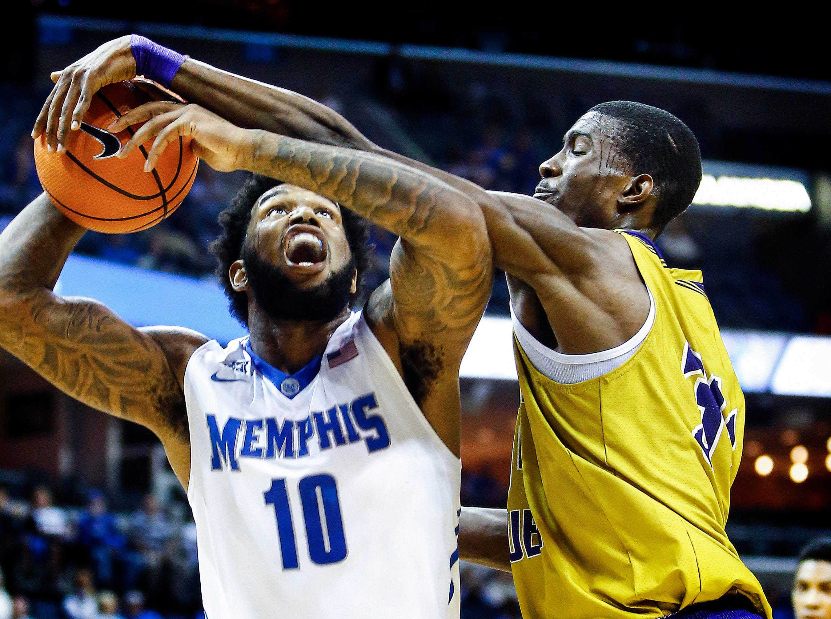 University of Memphis forward Mike Parks Jr. (left) is fouled by LeMoyne-Owen defender Kemar Campbell (right) during first half action at the FedExForum in Memphis, Tenn., Thursday, November 2, 2017.